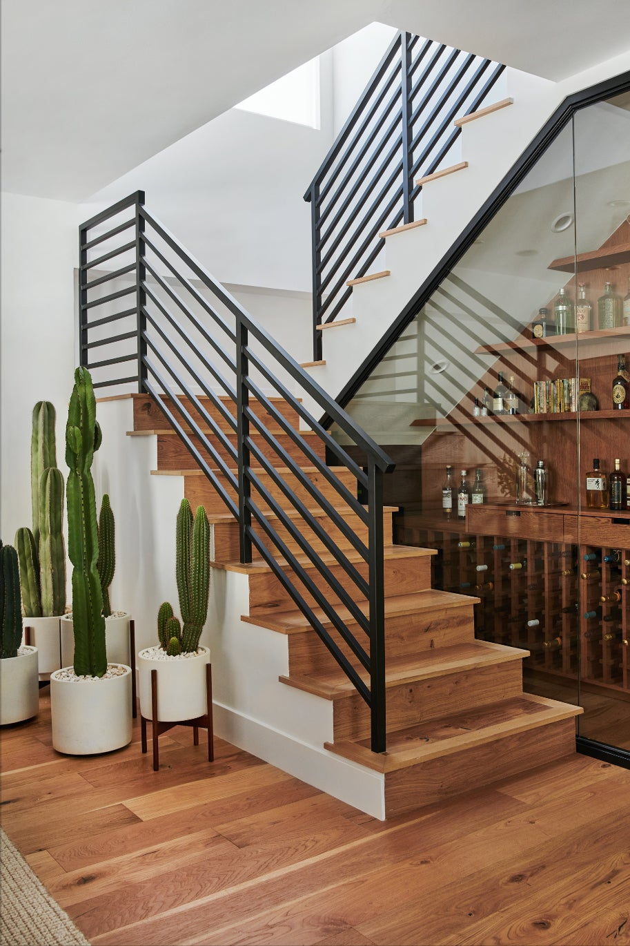 modern staircase with a glass enclosed bar underneath