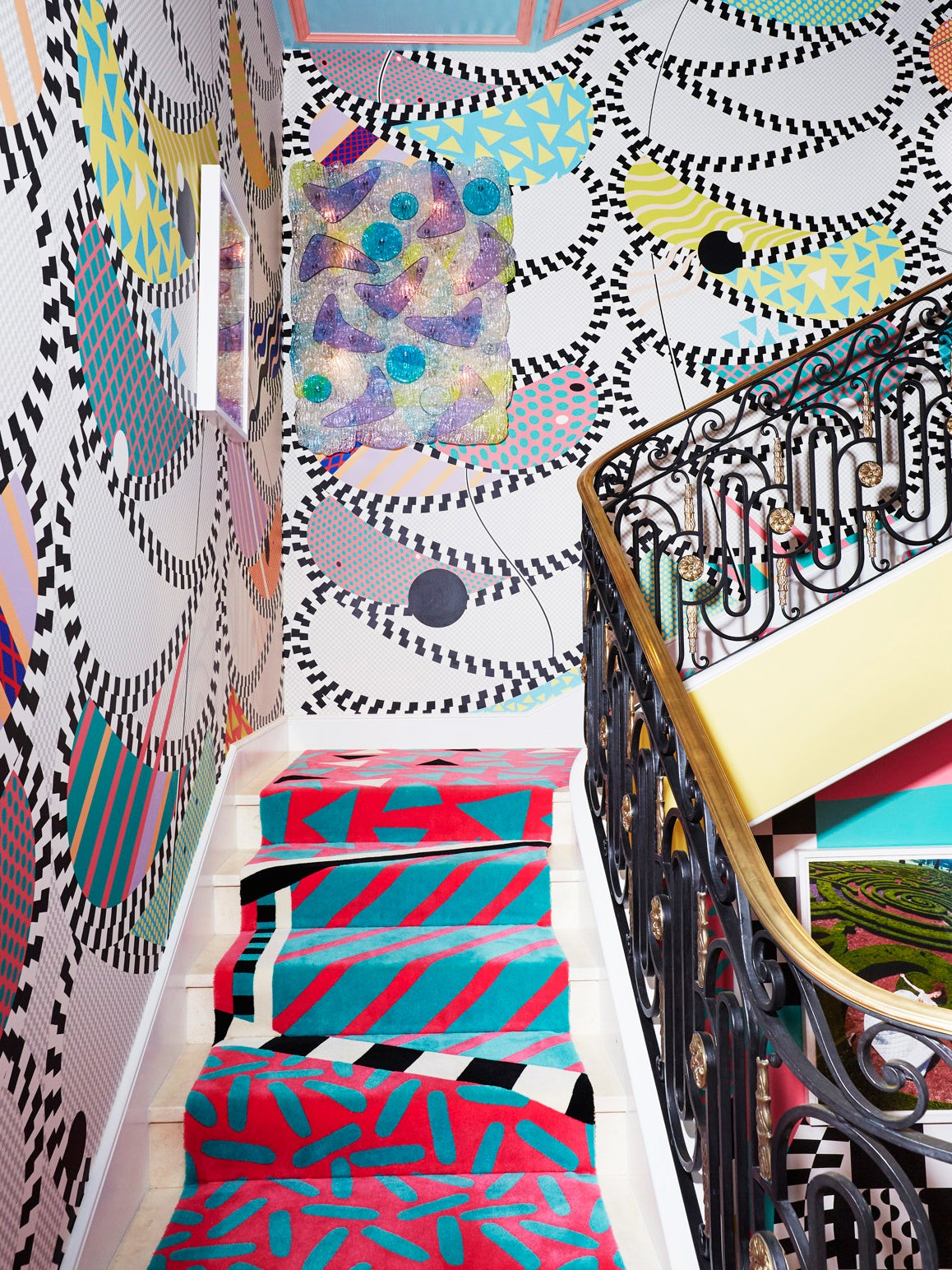 colorful, maximalist staircase with pink and blue runner and paisely pattern wallpaper