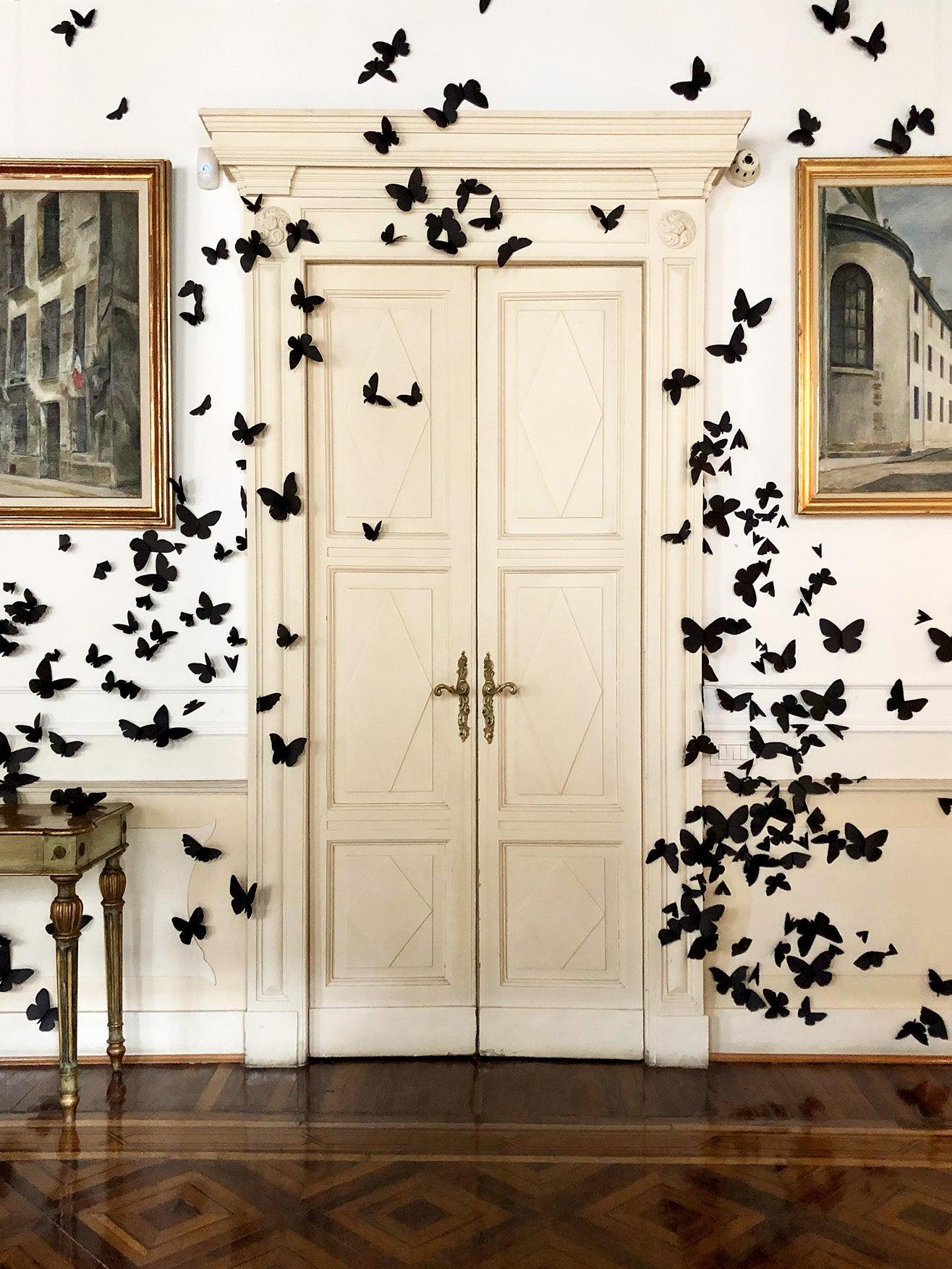 black butterflies swarm around an old doorway