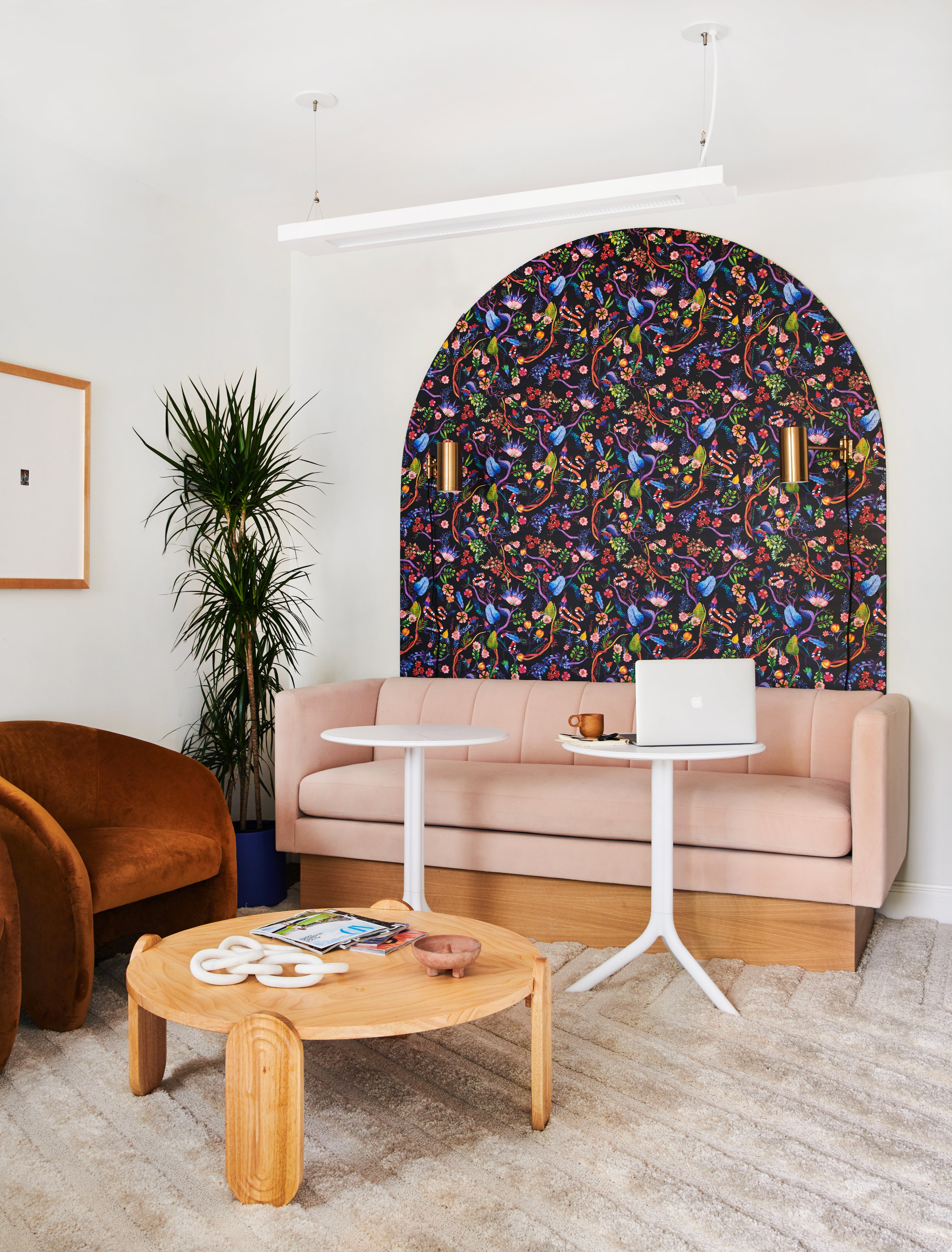pink sofa elevated on wood block with a bold wallpaper arch behind it