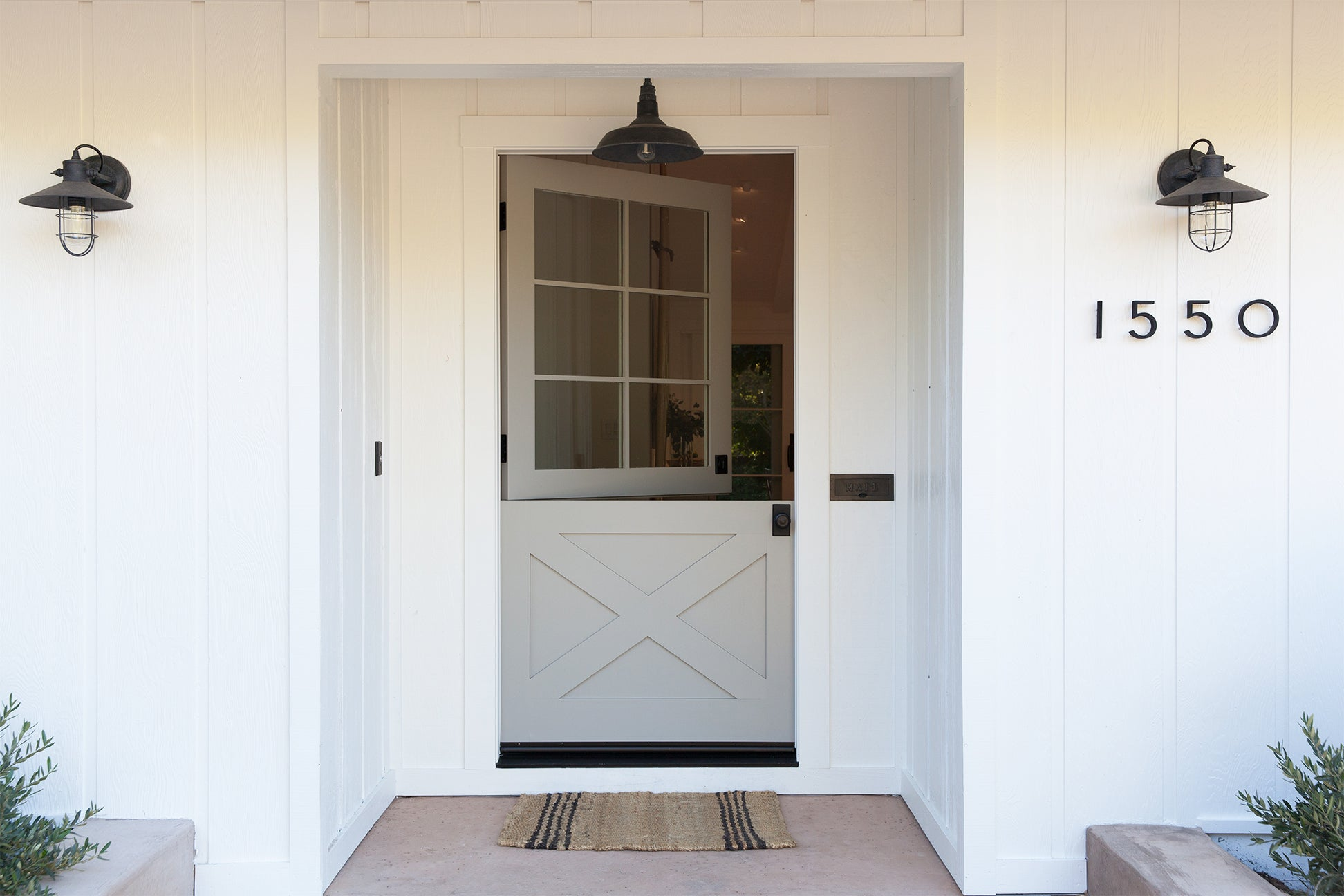 tan colored dutch door with a plain welcome mat and white exterior house
