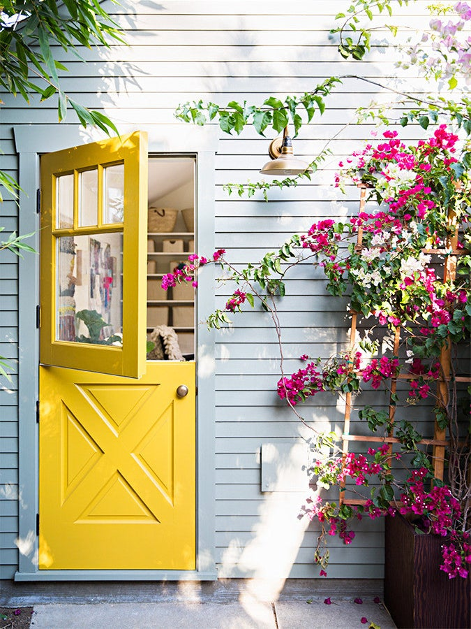 bright yellow dutch door surrounded by pink flowers