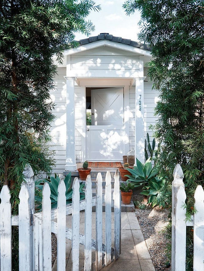 white cottage with a white picket fence