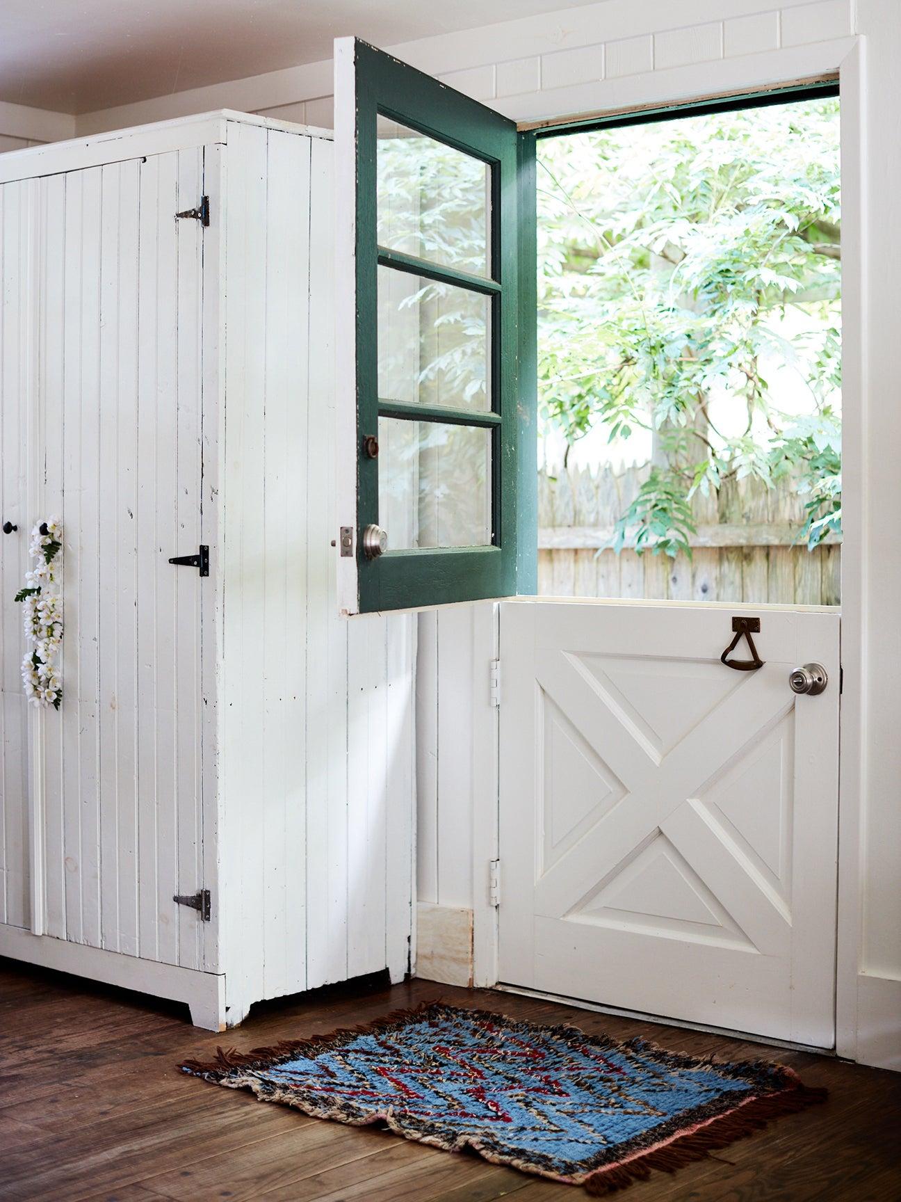 indoor view of a half open dutch door with a green top