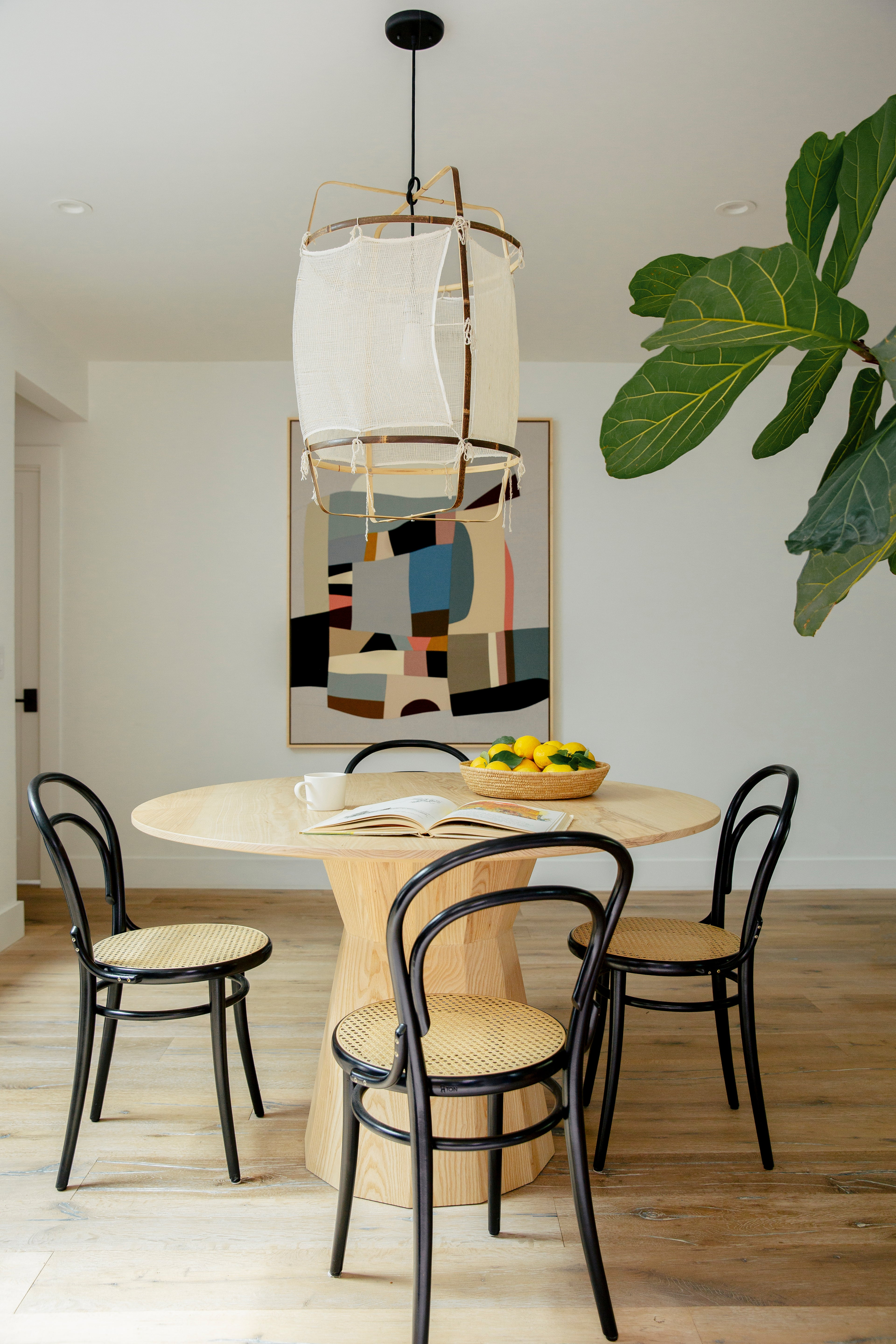 dining room with light wood table, black and cane dining chairs