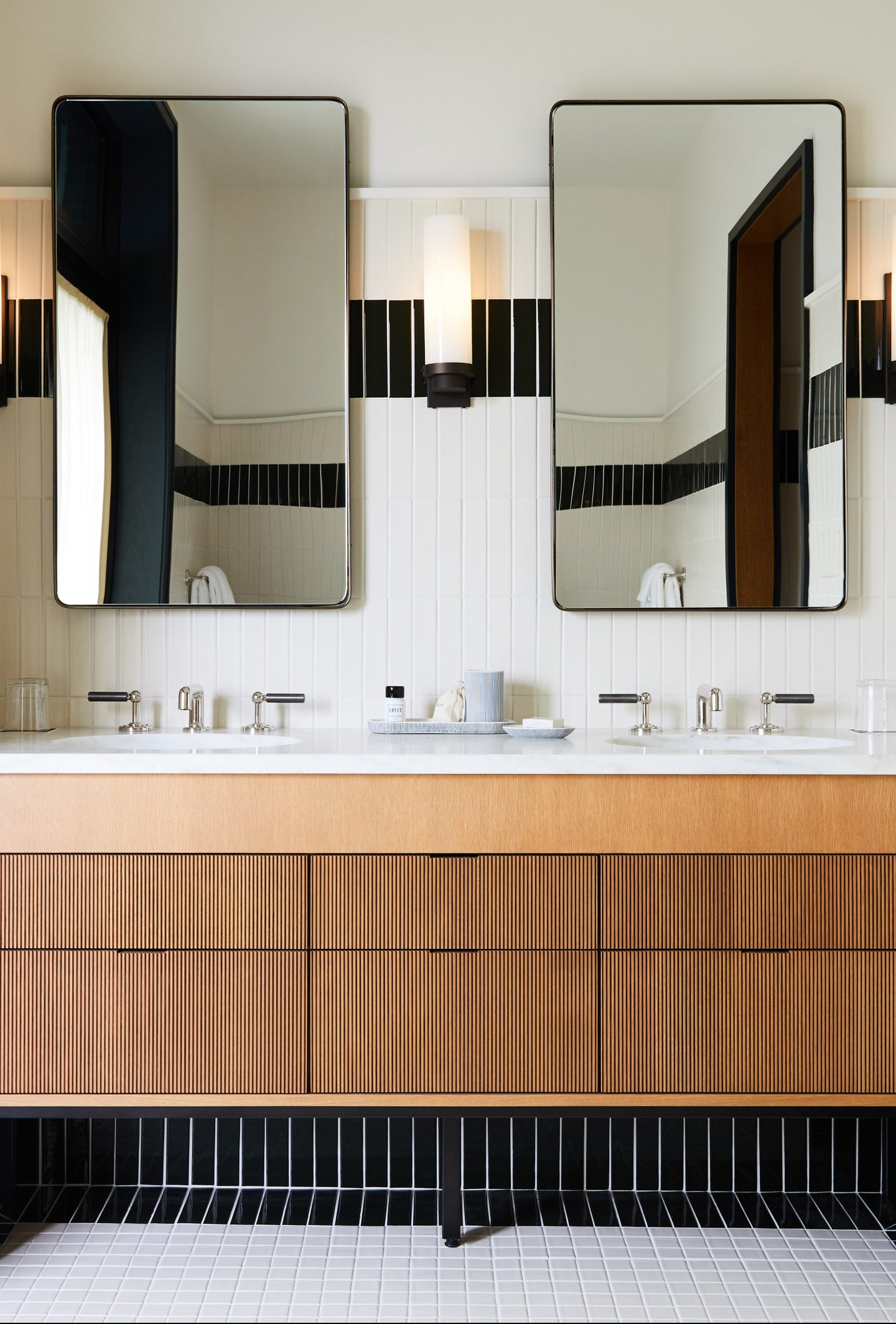 wood bathroom vanity surrounded by marble walls and counter