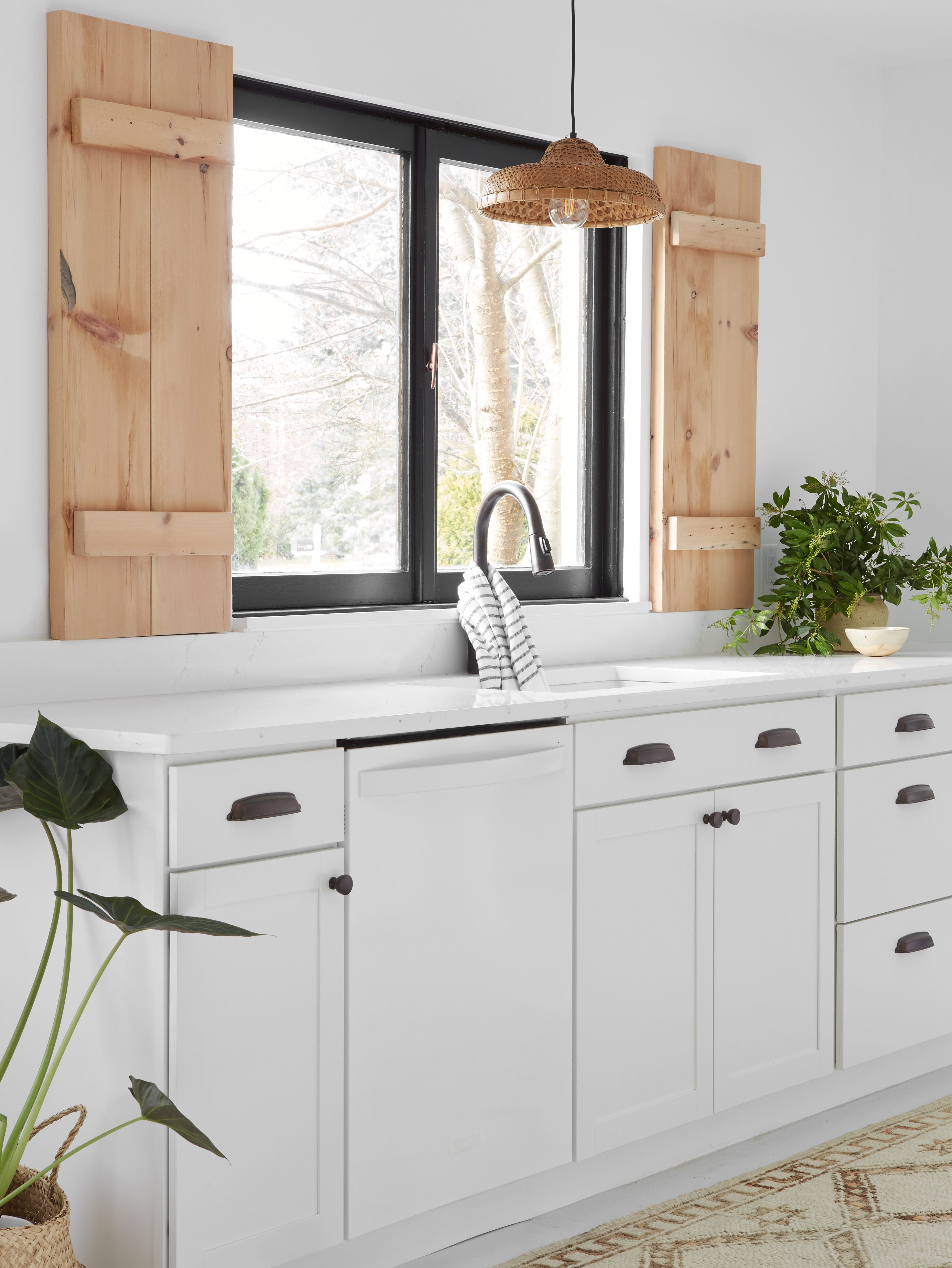 white kitchen sink area with raw wood shutters by the window