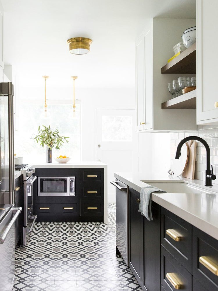 black white and brass kitchen with mosaic floor tiles