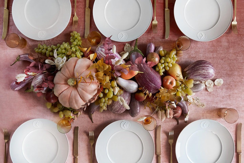 birds eye shot of white plates on a pink velvet table