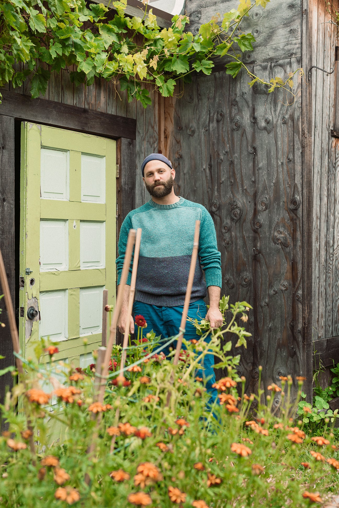 man standing in front of weathered home exterior with plants