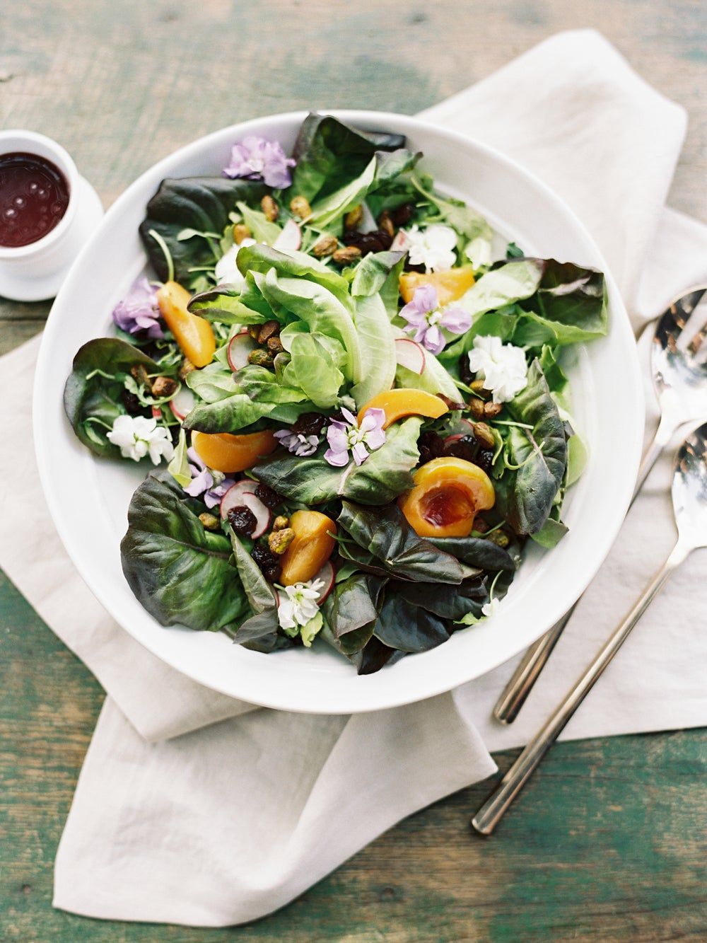 white bowl with salad of dark greens, oranges, lilac flowers