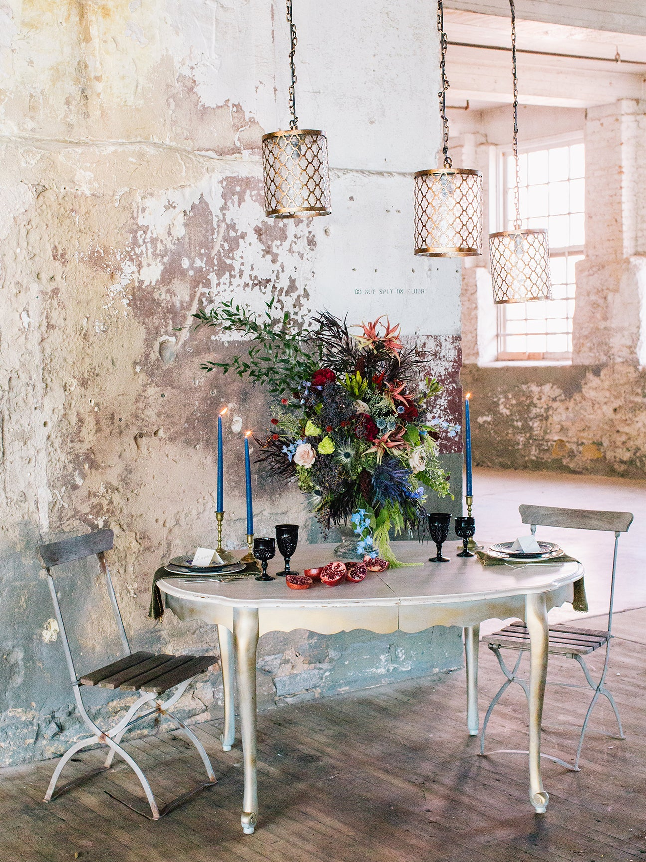 room with textured walls and floors, a small table and two chairs, floral arrangement and table settings