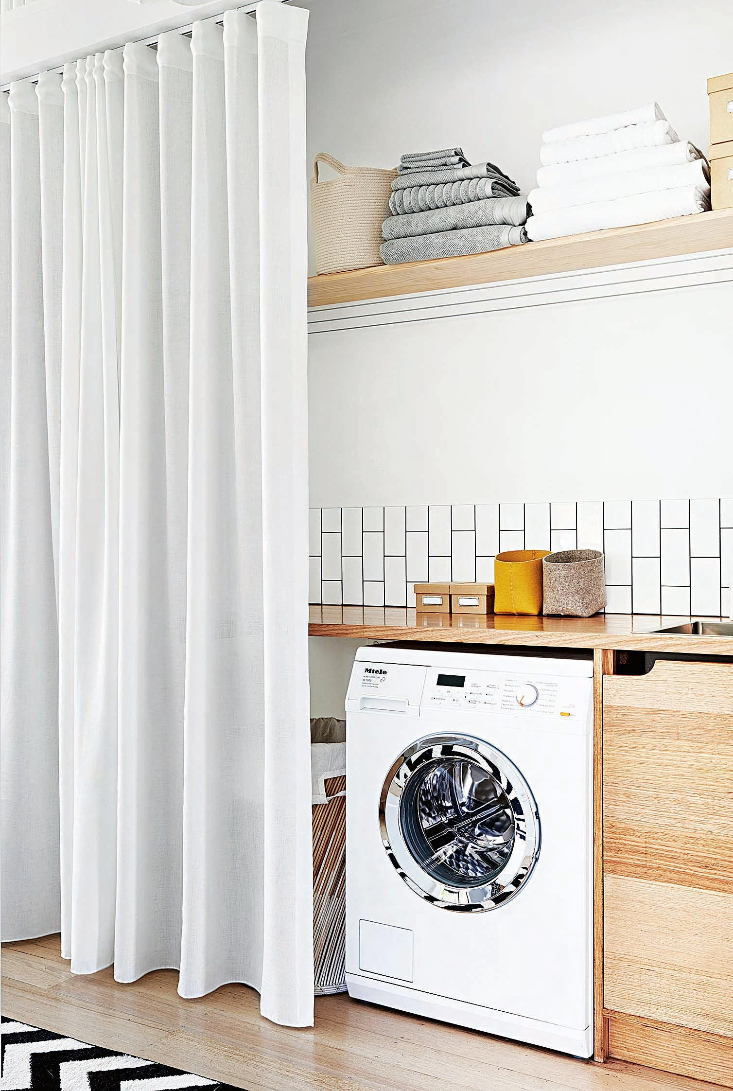 laundry closet with wood counter and white curtain