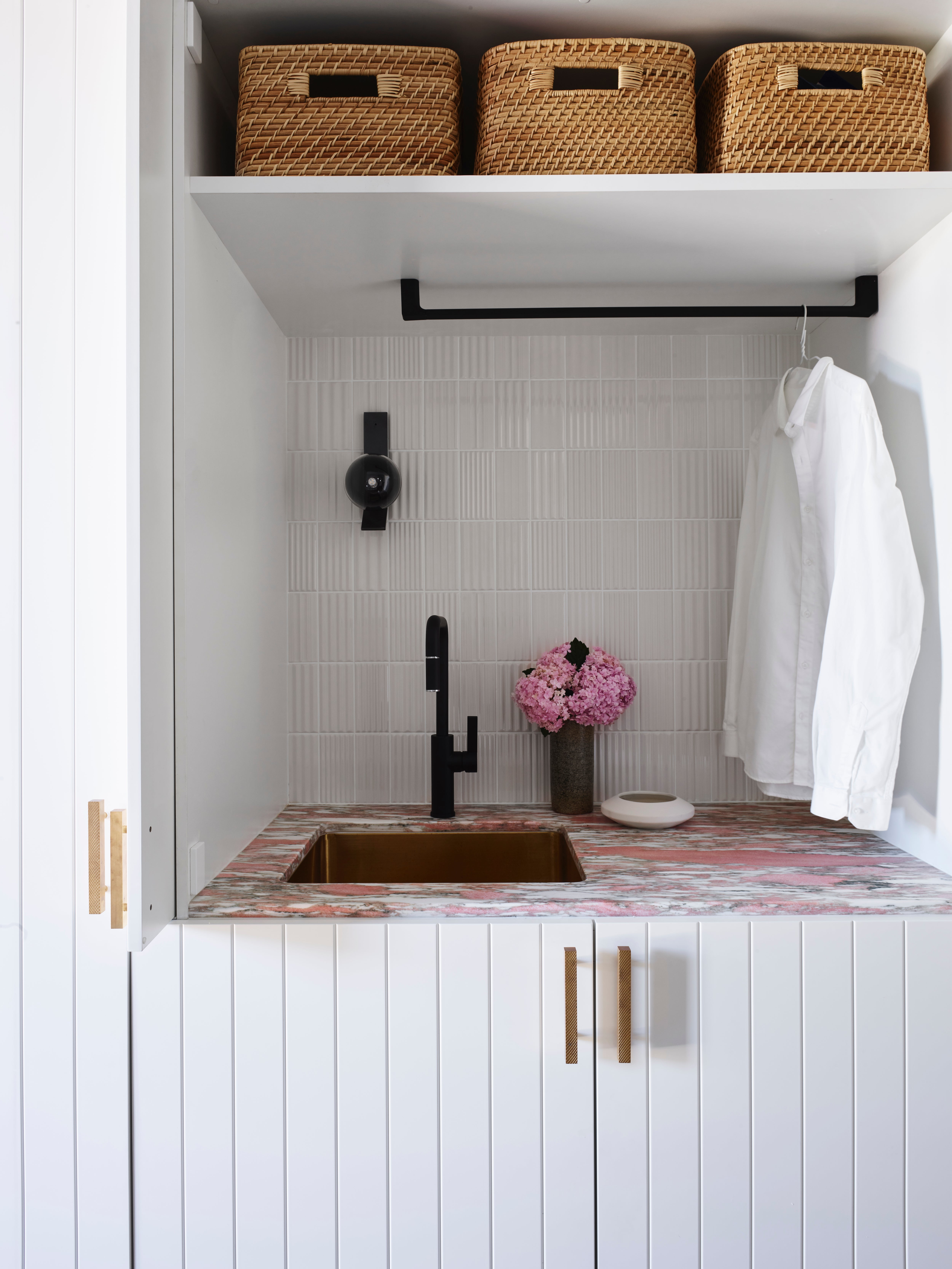 pink marble tiled counter wiht brass sink