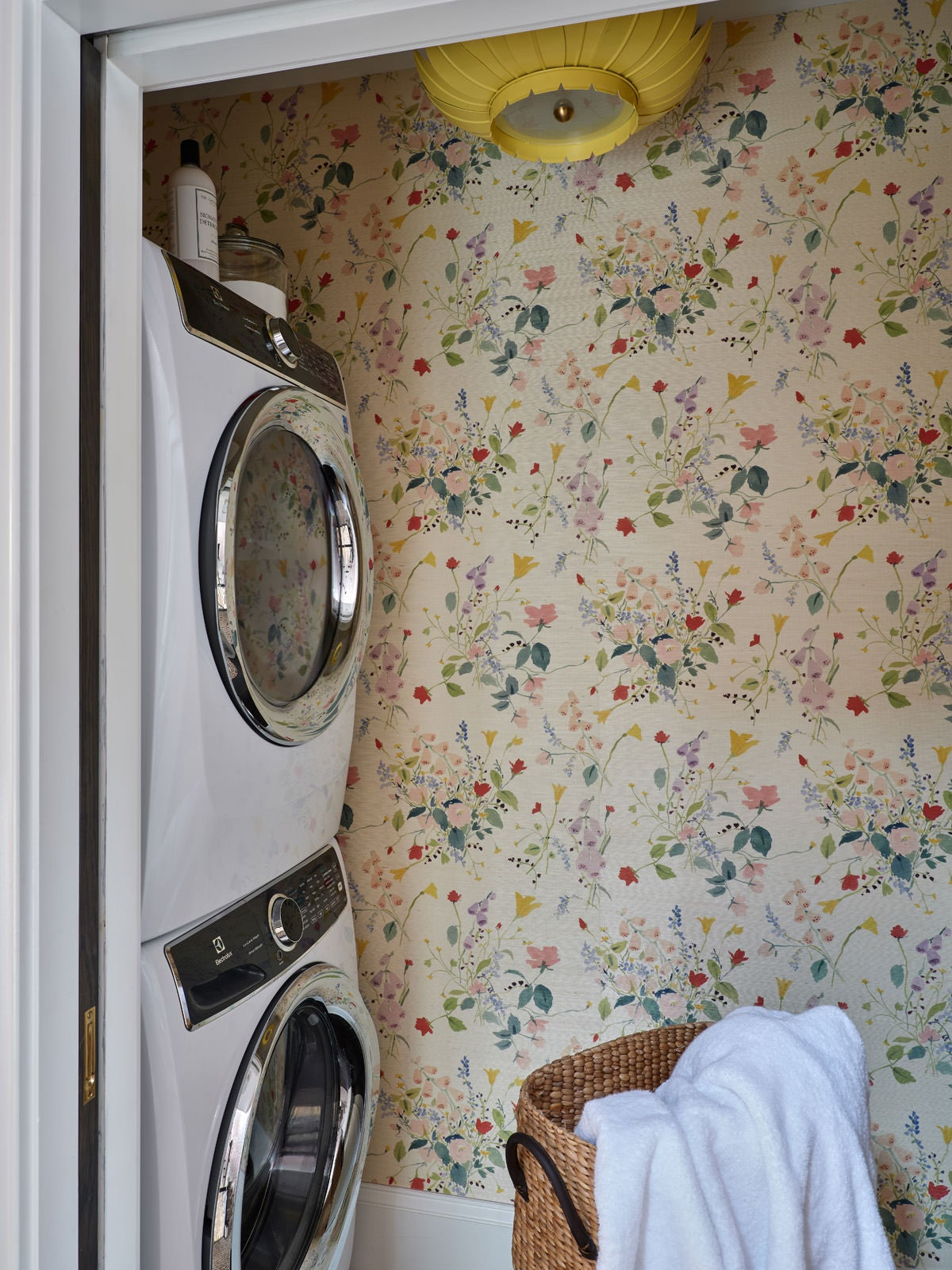 floral wallpaper with washer and dryer stacked to the side wall