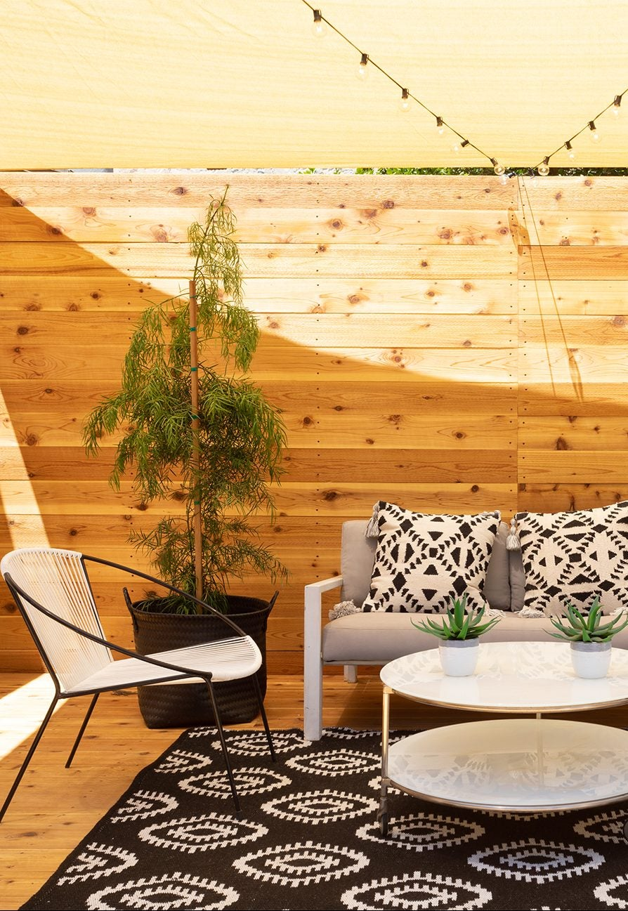 shaded wood deck porch with white and black furniture