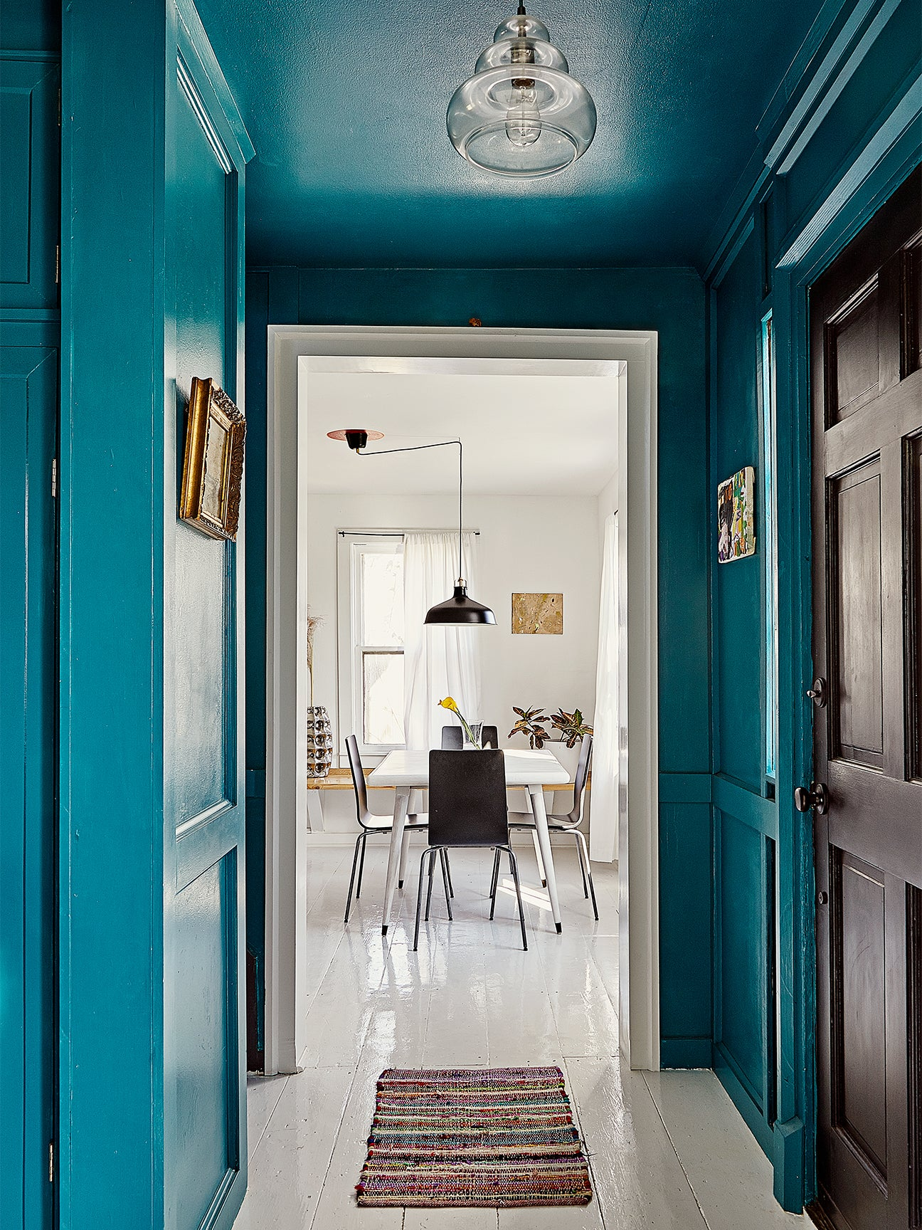 blue hallway leading to an all white dining room