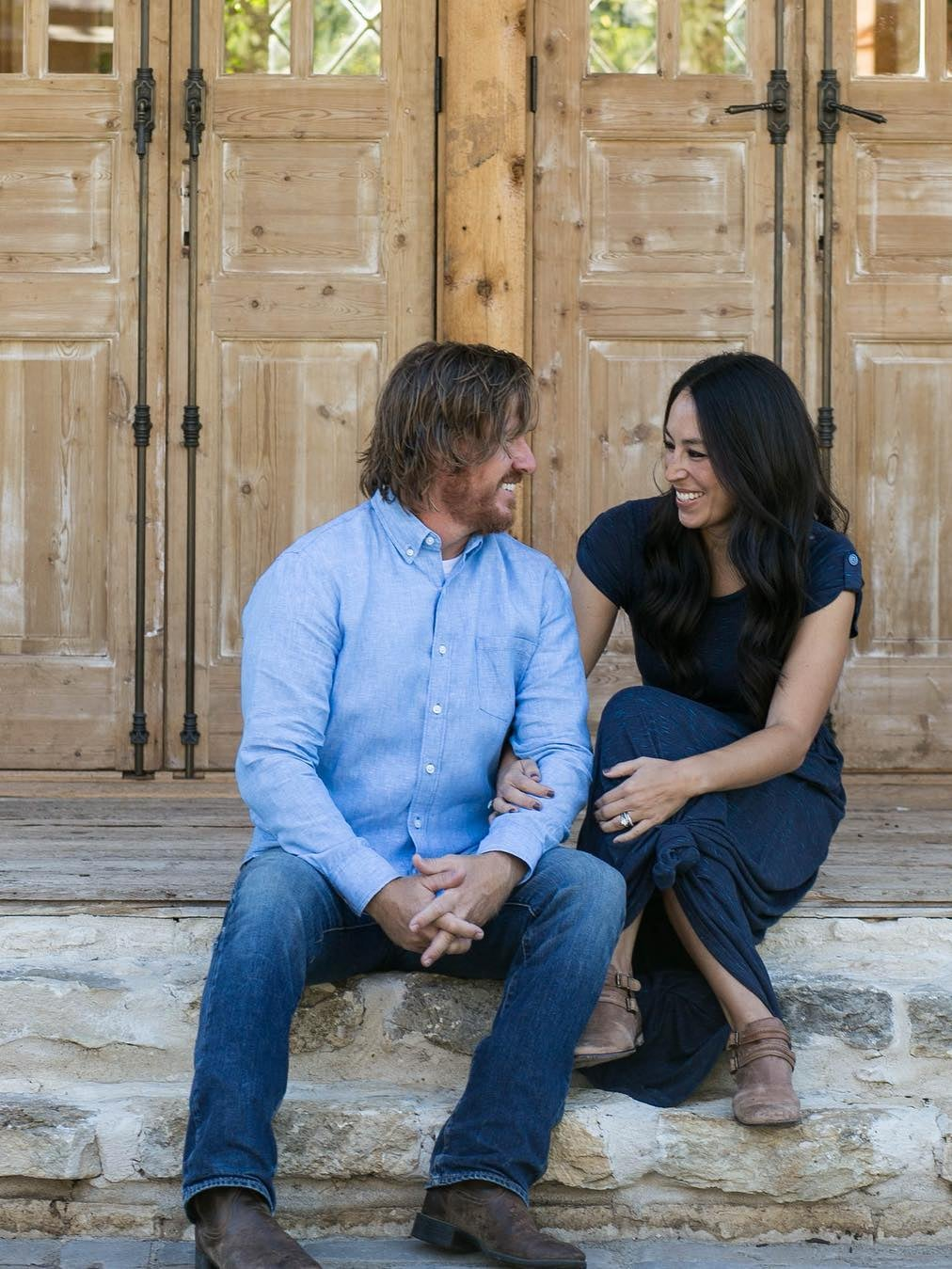 chip and joanna gaines sitting on steps looking at each other