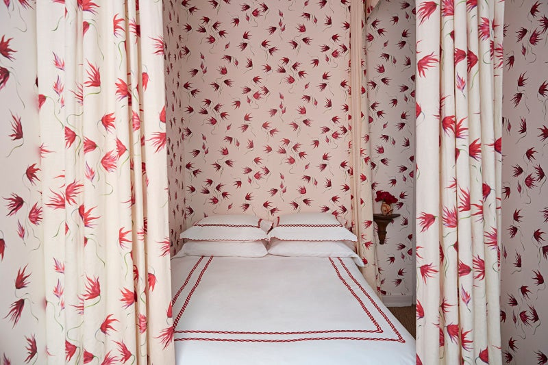 red floral drapery around a bed that matches the walls
