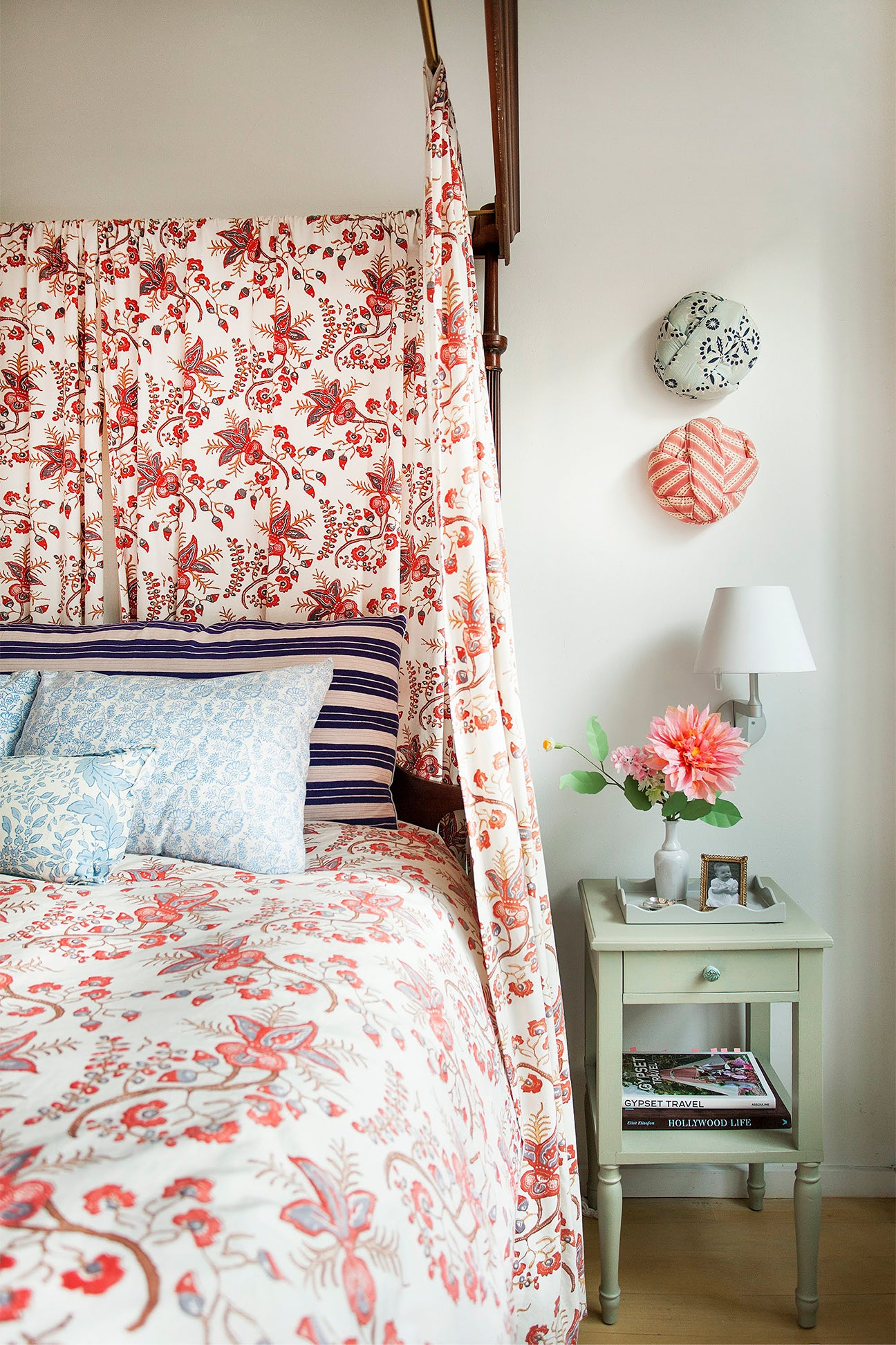bed cloacked in red floral fabric
