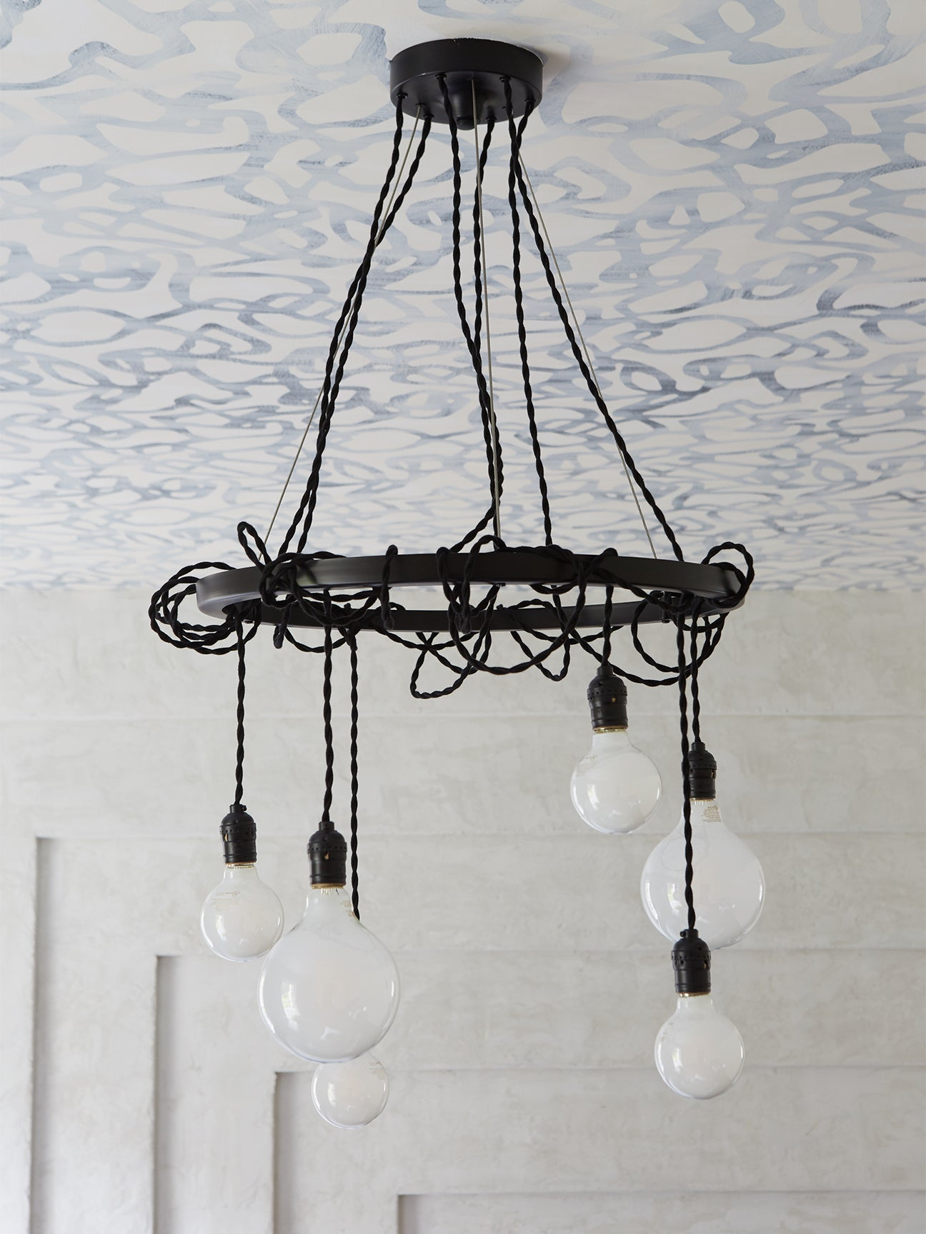 light bulbs on ropes hanging from a circular chandelier