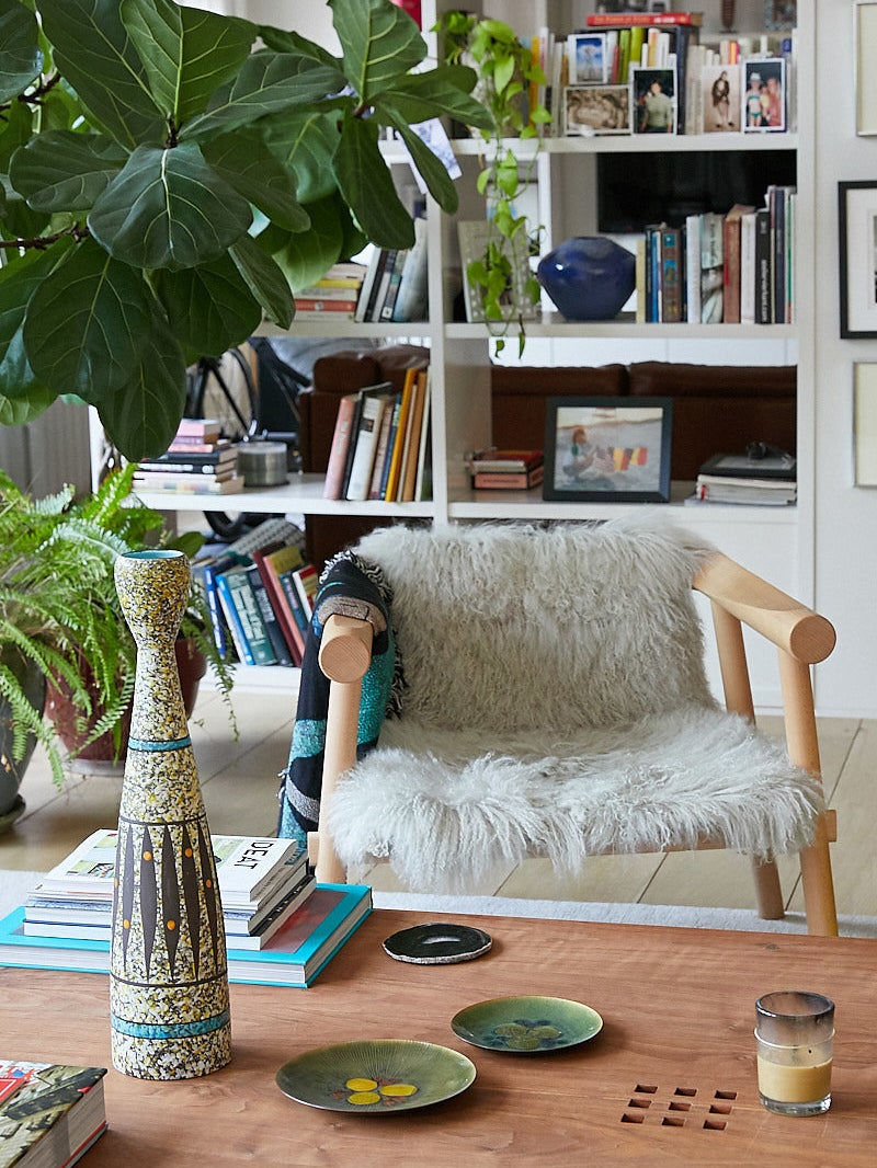 eclectic living room with a wood chair with a sheepskin throw on it