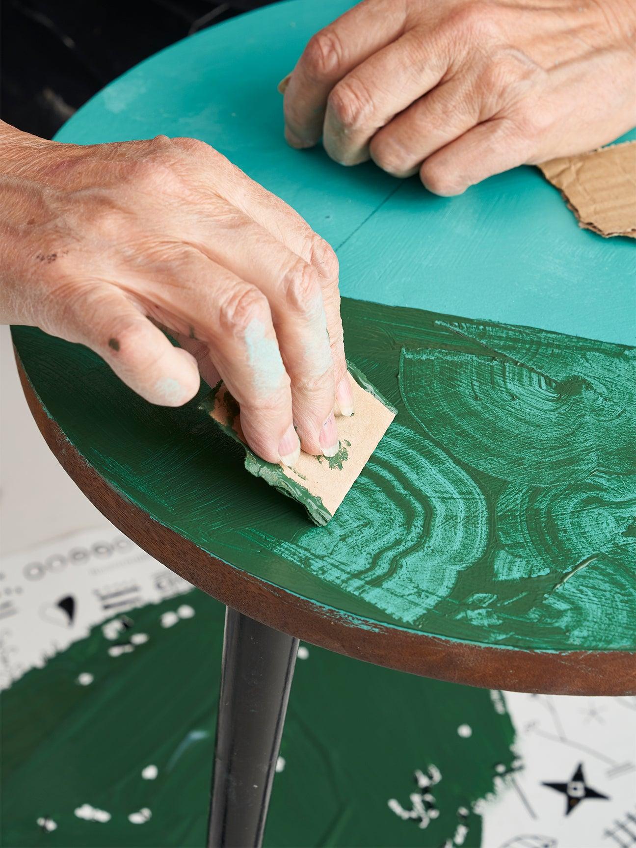 taking cardboard to a table to create swirl design