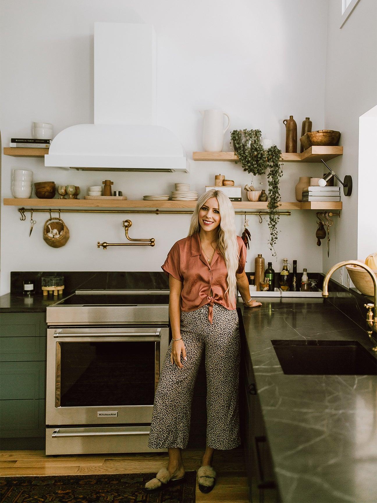 woman standing in dark green kitchen with white hood