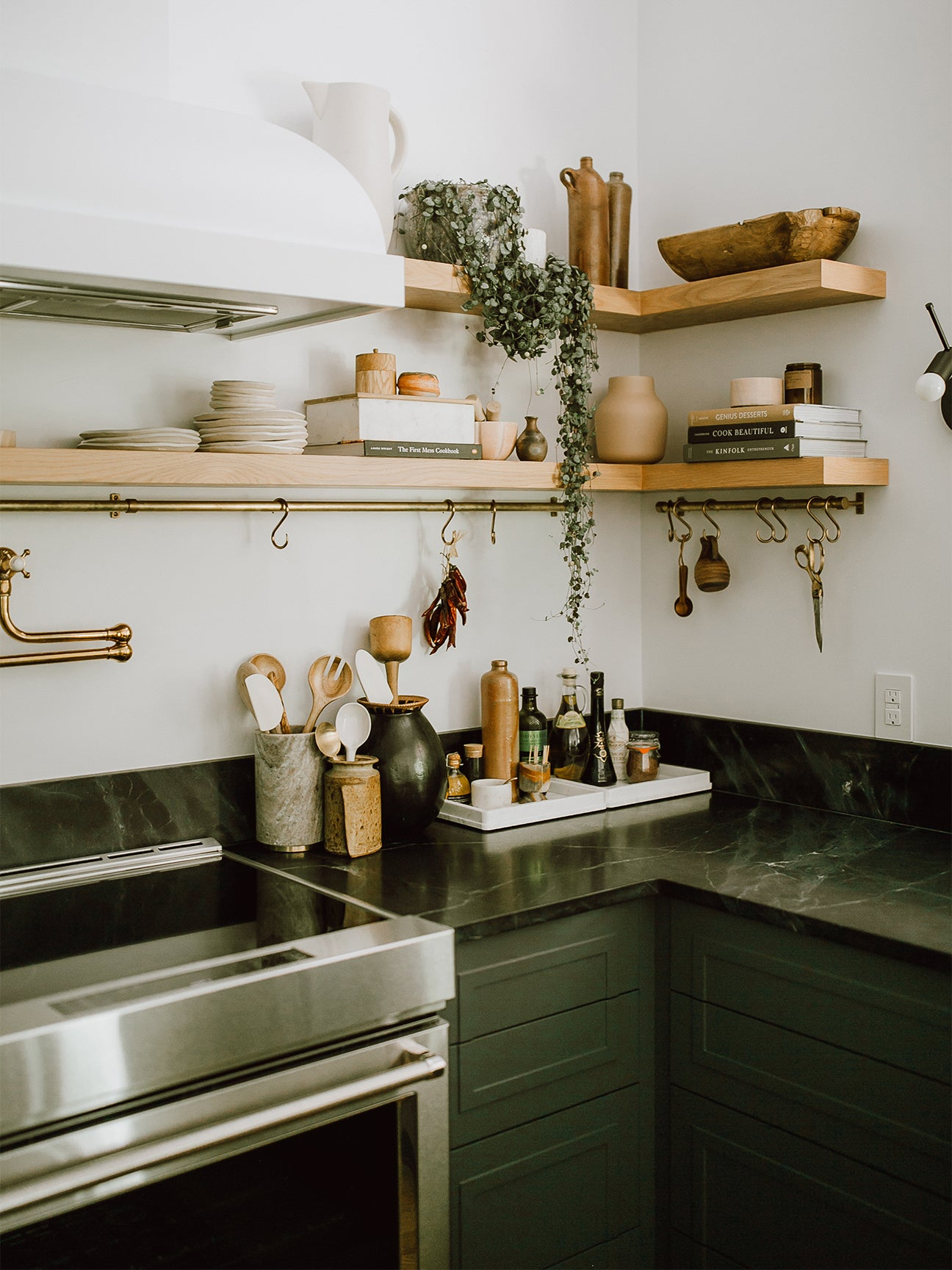 floating wood shelves with dark green kitchen with white hood