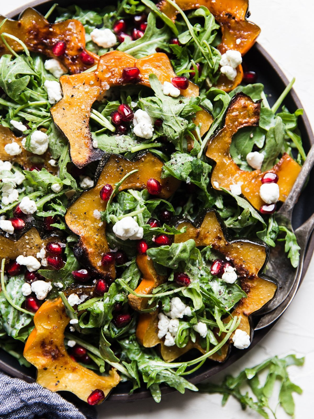 Salad with acorn squash slices, goat cheese dressing, and pomegranate seeds.