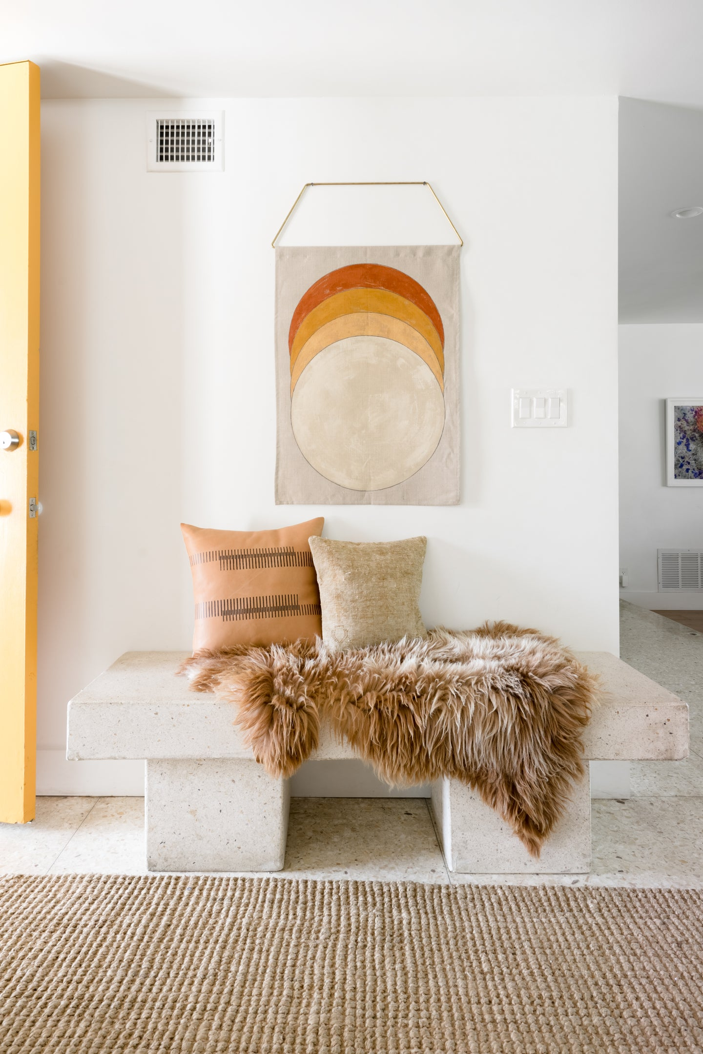 Entryway with concrete bench and wall hanging