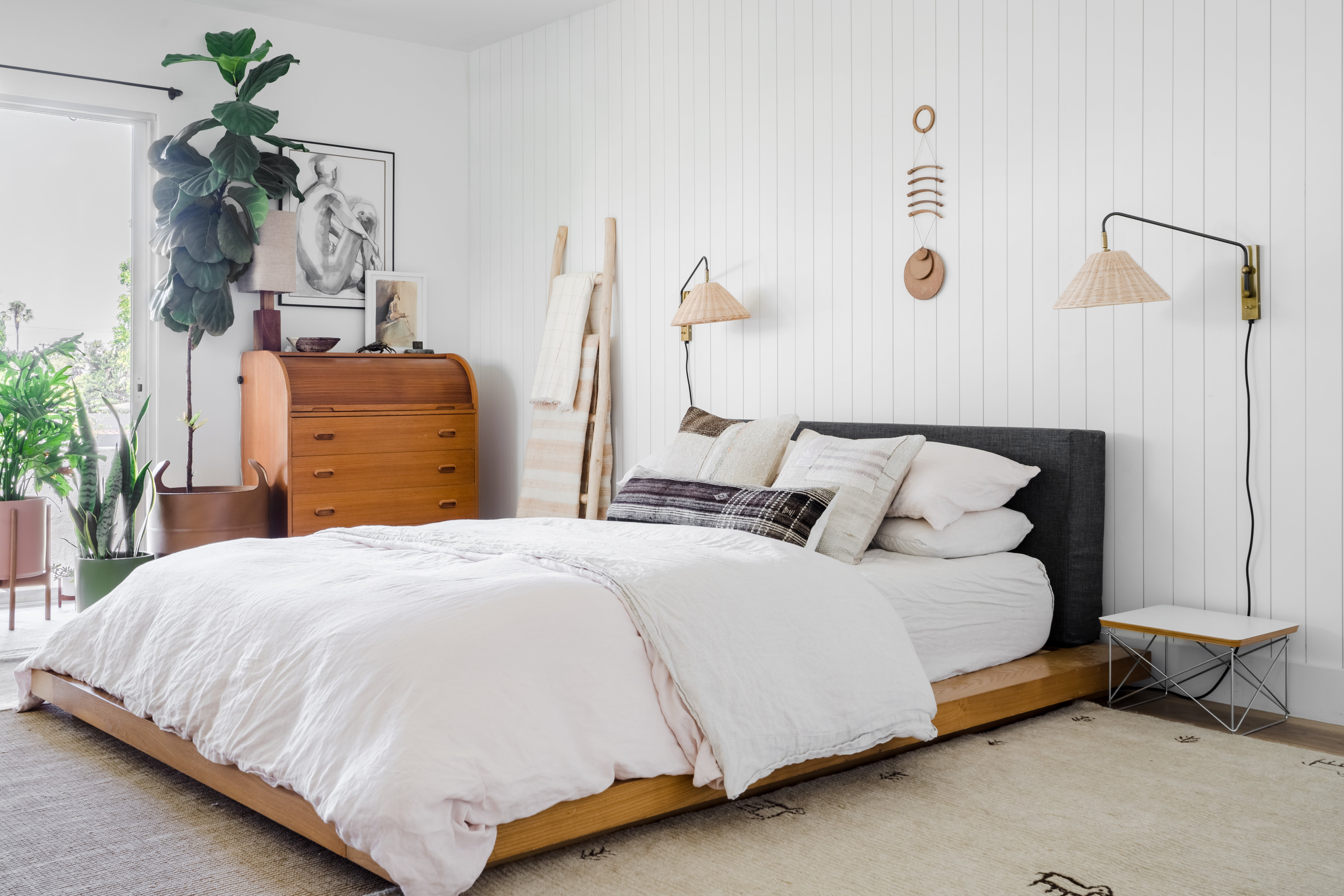 Bedroom with shiplap walls and rattan sconces