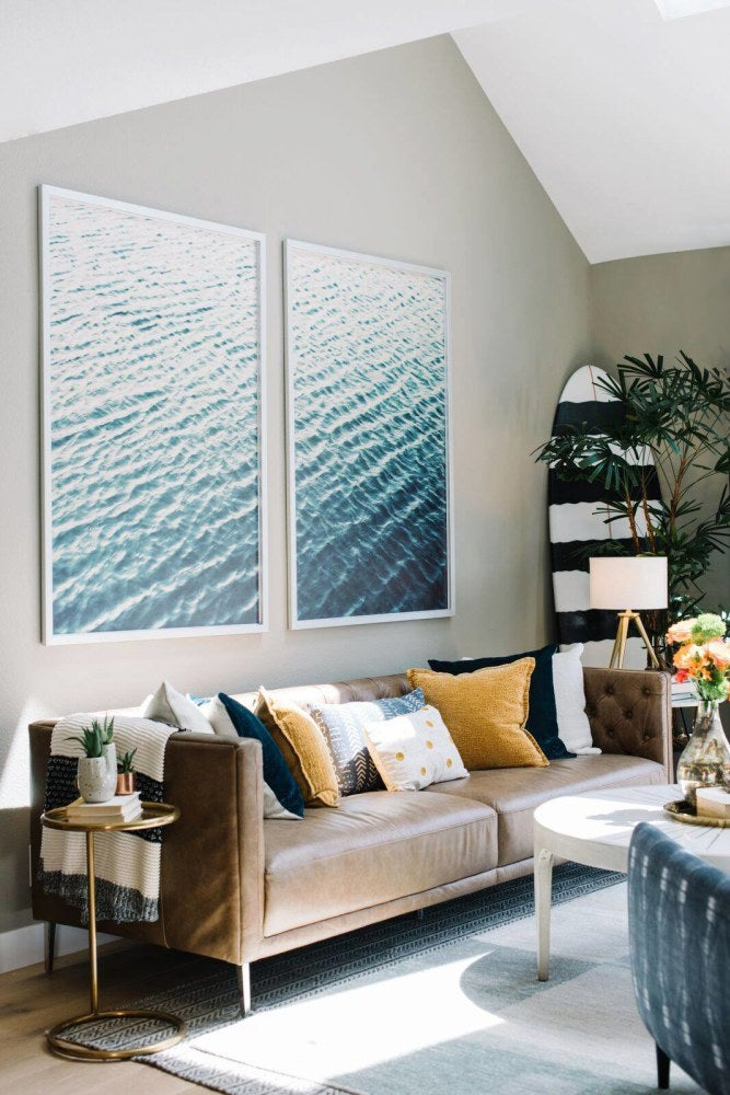 large scale prints of water above living room sofa