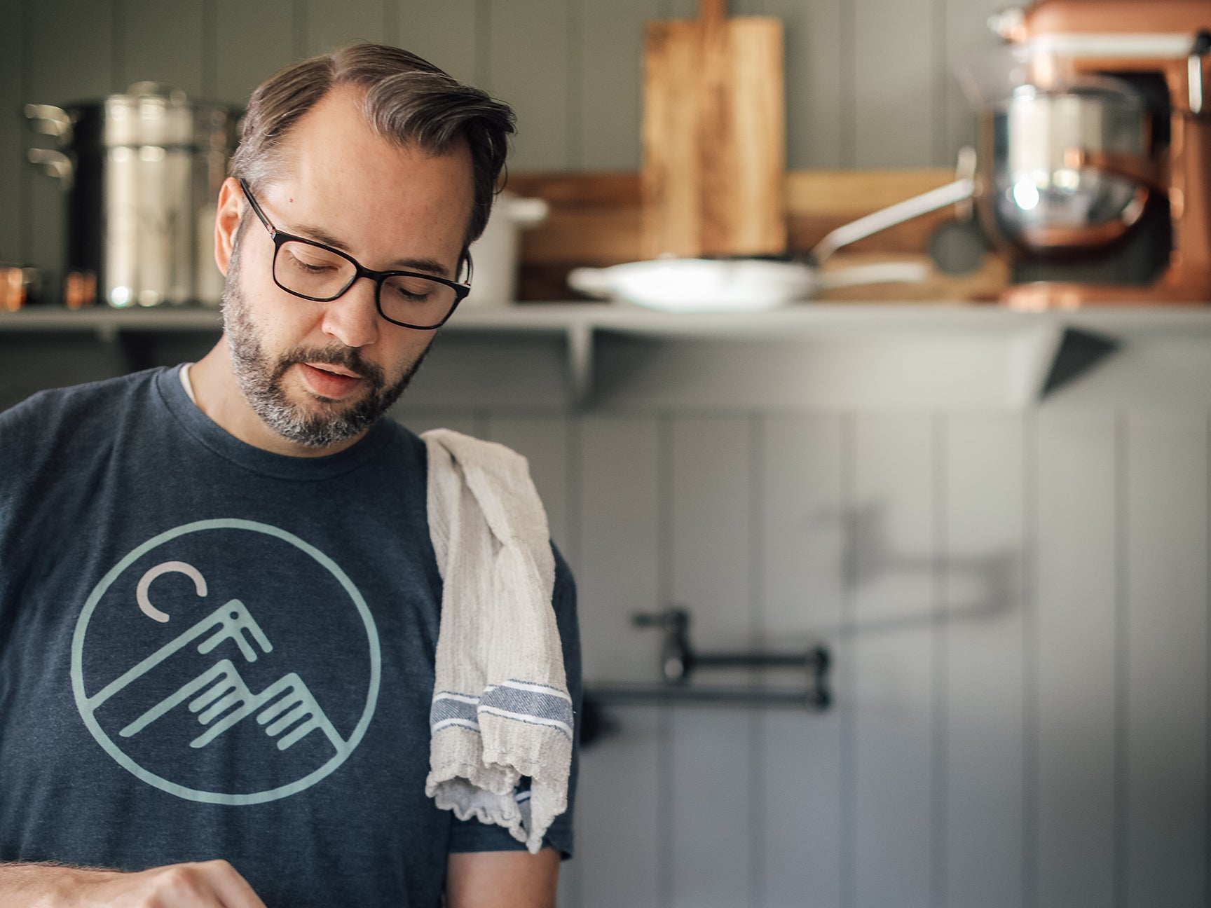 man cooking with a rag on his shoulder