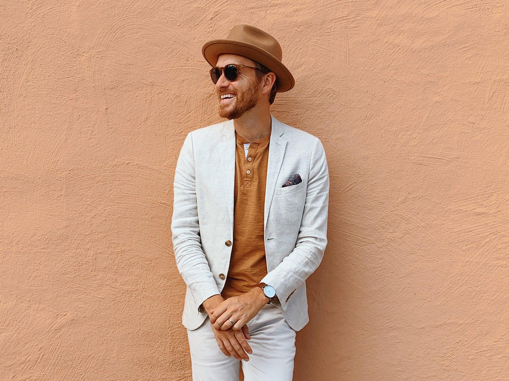 man leaning against a orange wall