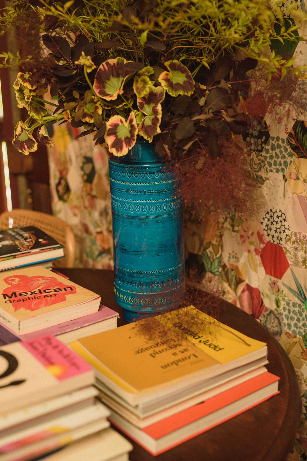 plant in blue vase next to stacks of books