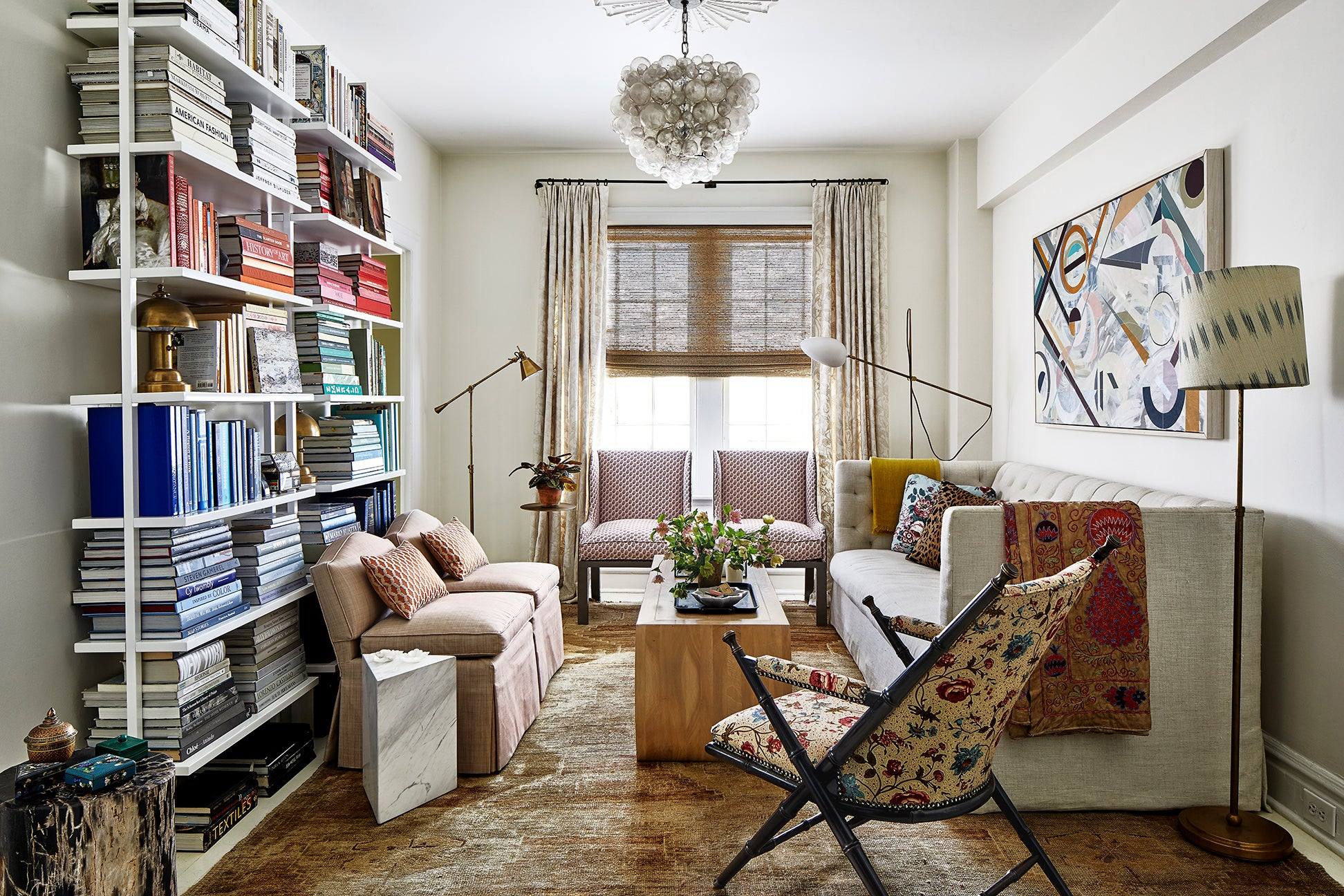 living room with color coordinated books on a shelf
