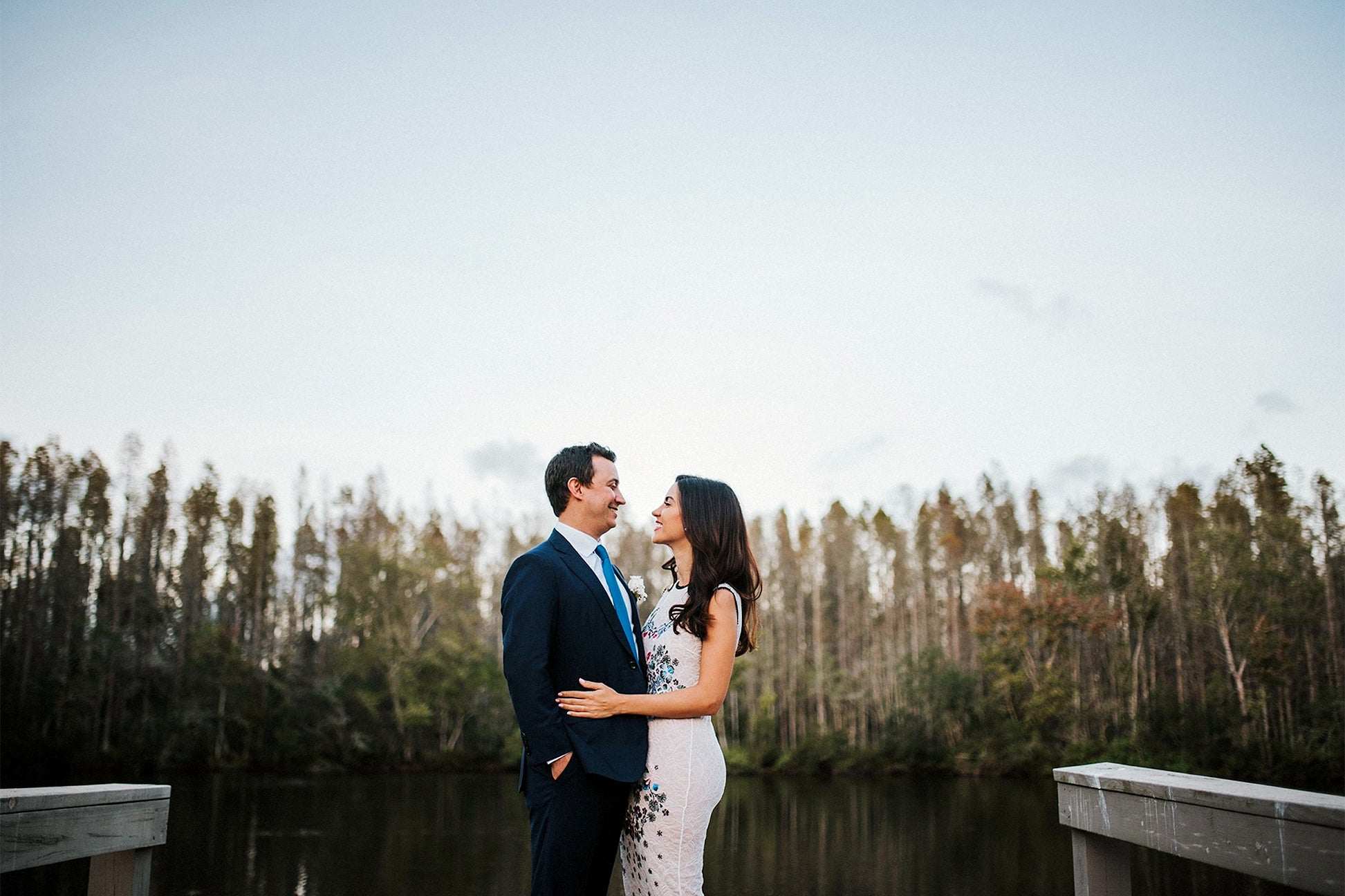 Couple by a lake on their wedding day