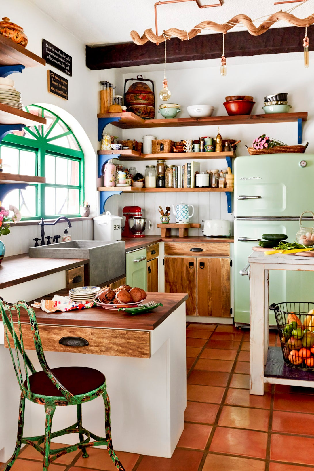 eclectic kitchen with green fridge and wooden cabinets