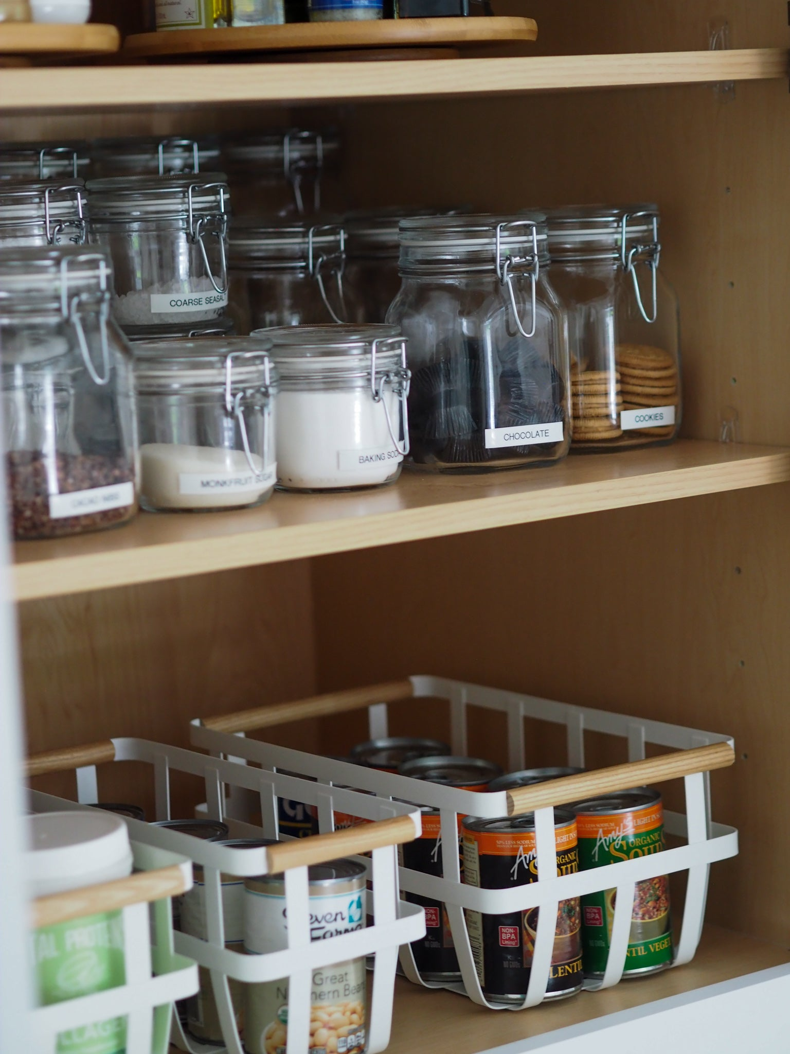 baskets and clear canisters on a shelf
