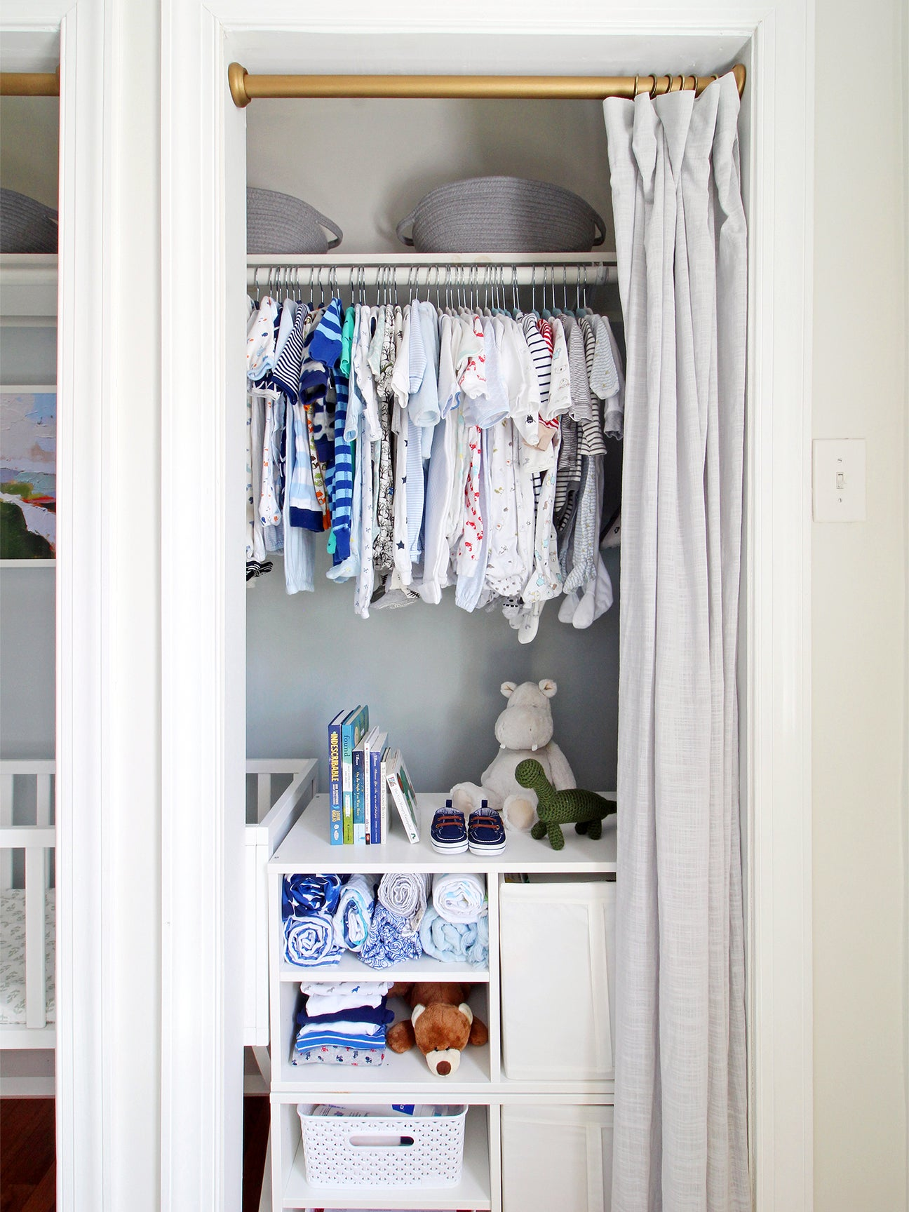 small closet with baby clothes and a curtian drawn back