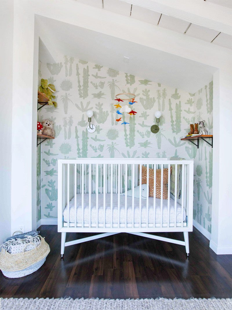 small nursery nook with a crib and cactus wallpaper print