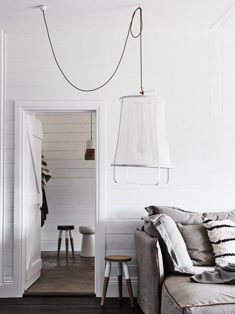 large white fabric pendant light next to a gray sofa