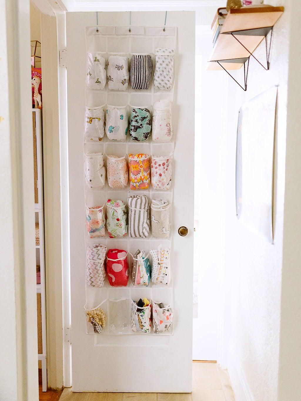 baby clothes hanging in an over the door shoe rack on the door