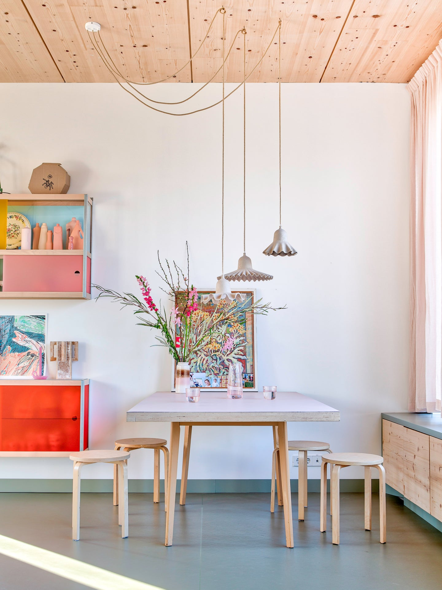 Kitchen with white walls, light wood table and chairs, and colorful wall cabinets