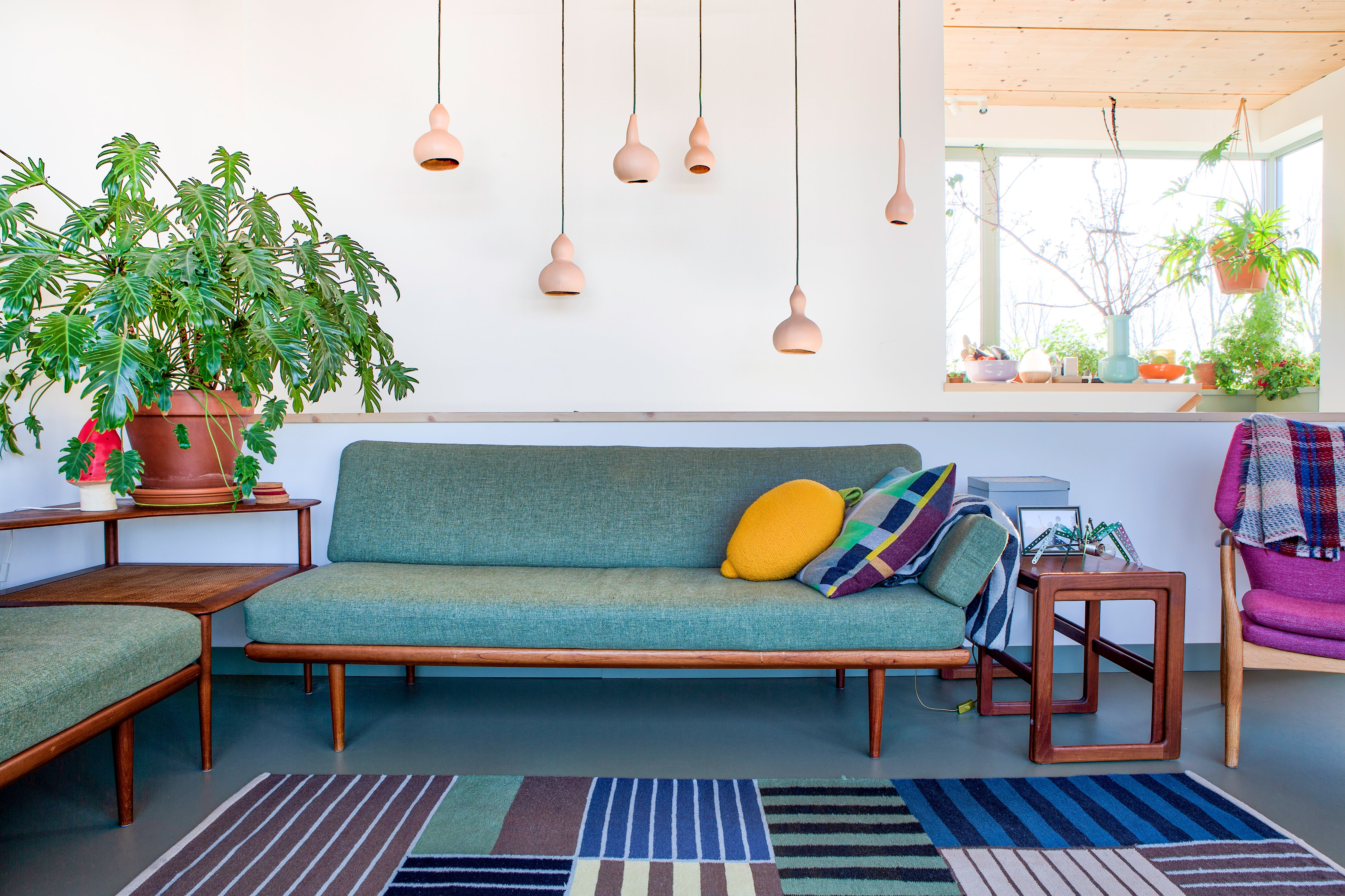 Living room with green sofa and striped blue rug