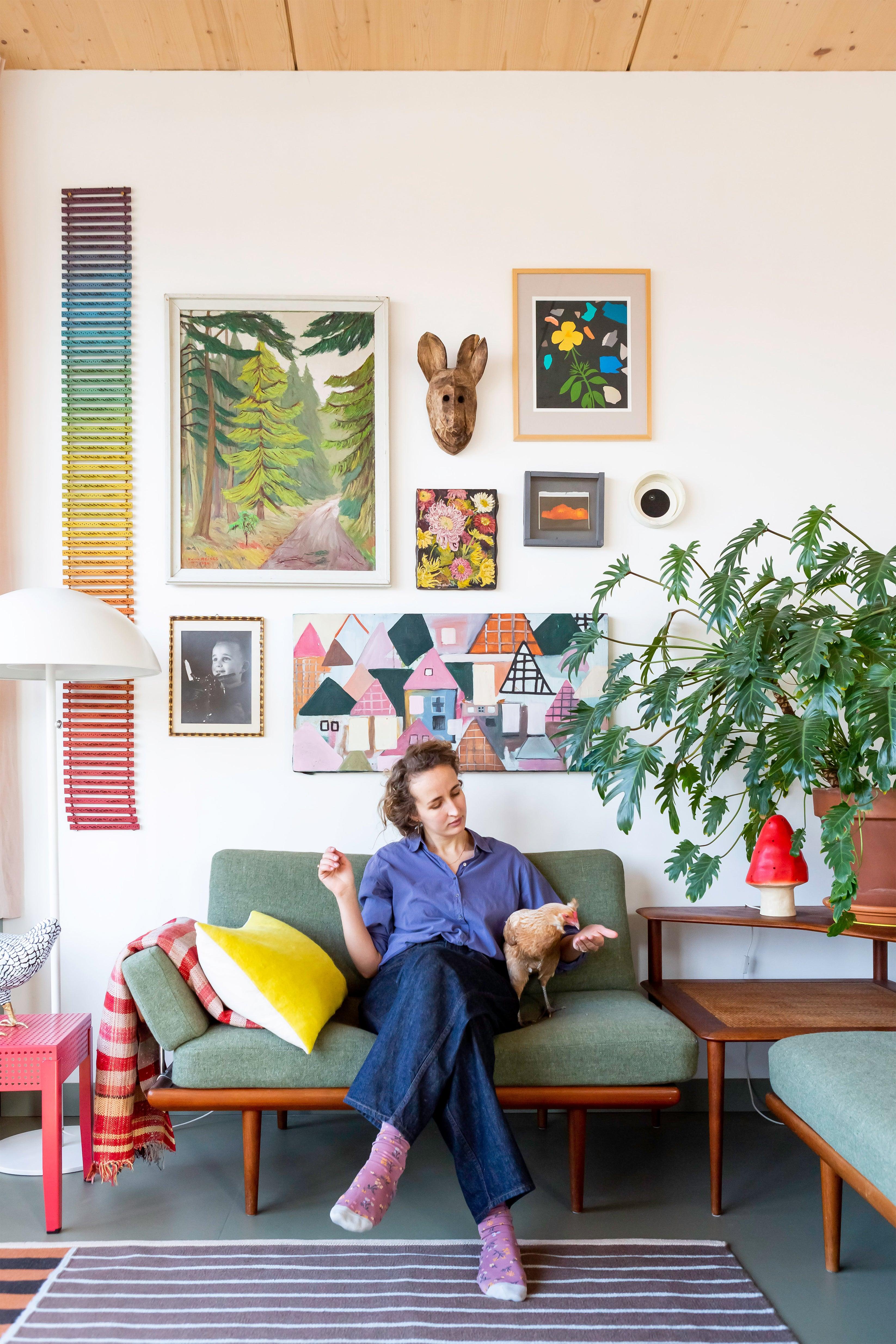 Foekje Fleur sitting on her sofa in front of a gallery wall