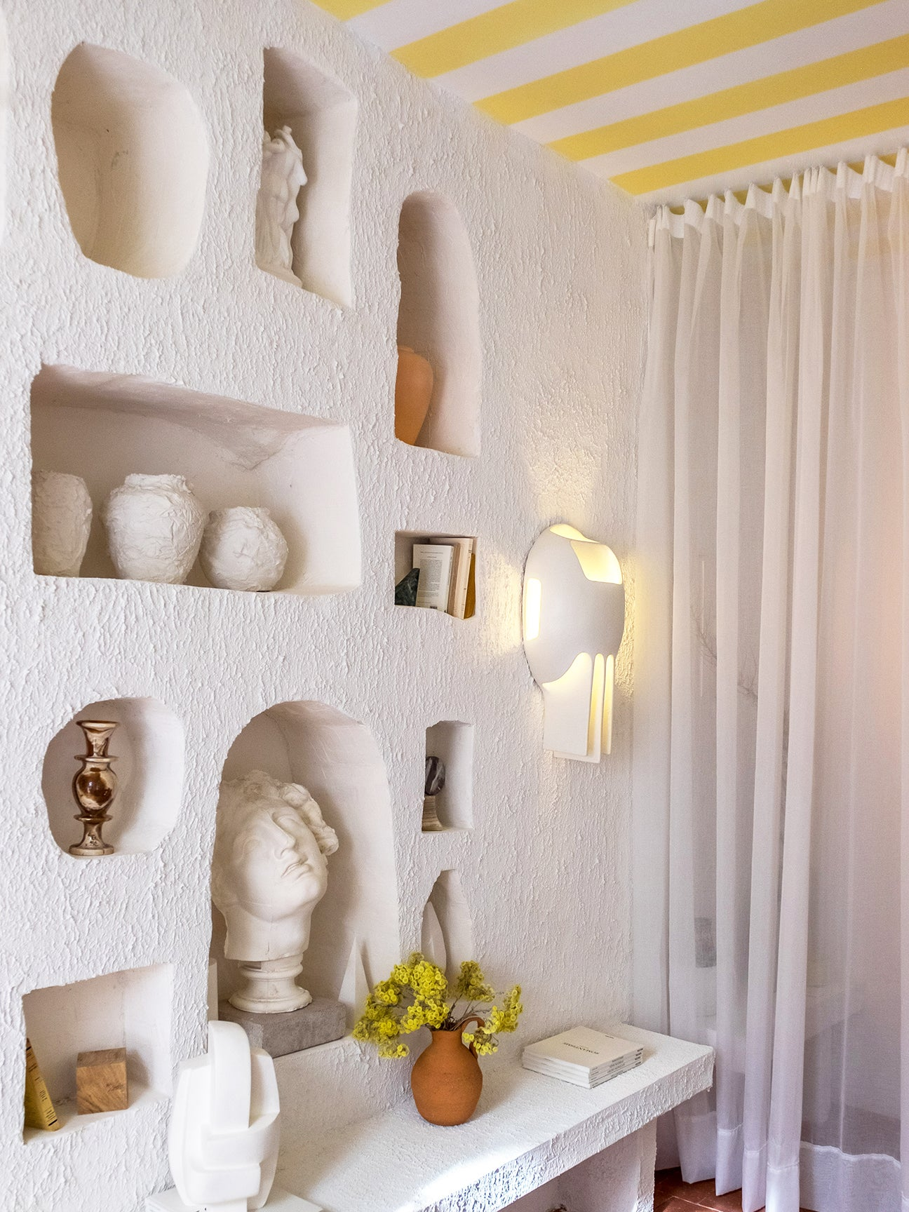 wall niches filled with vases and sculptures