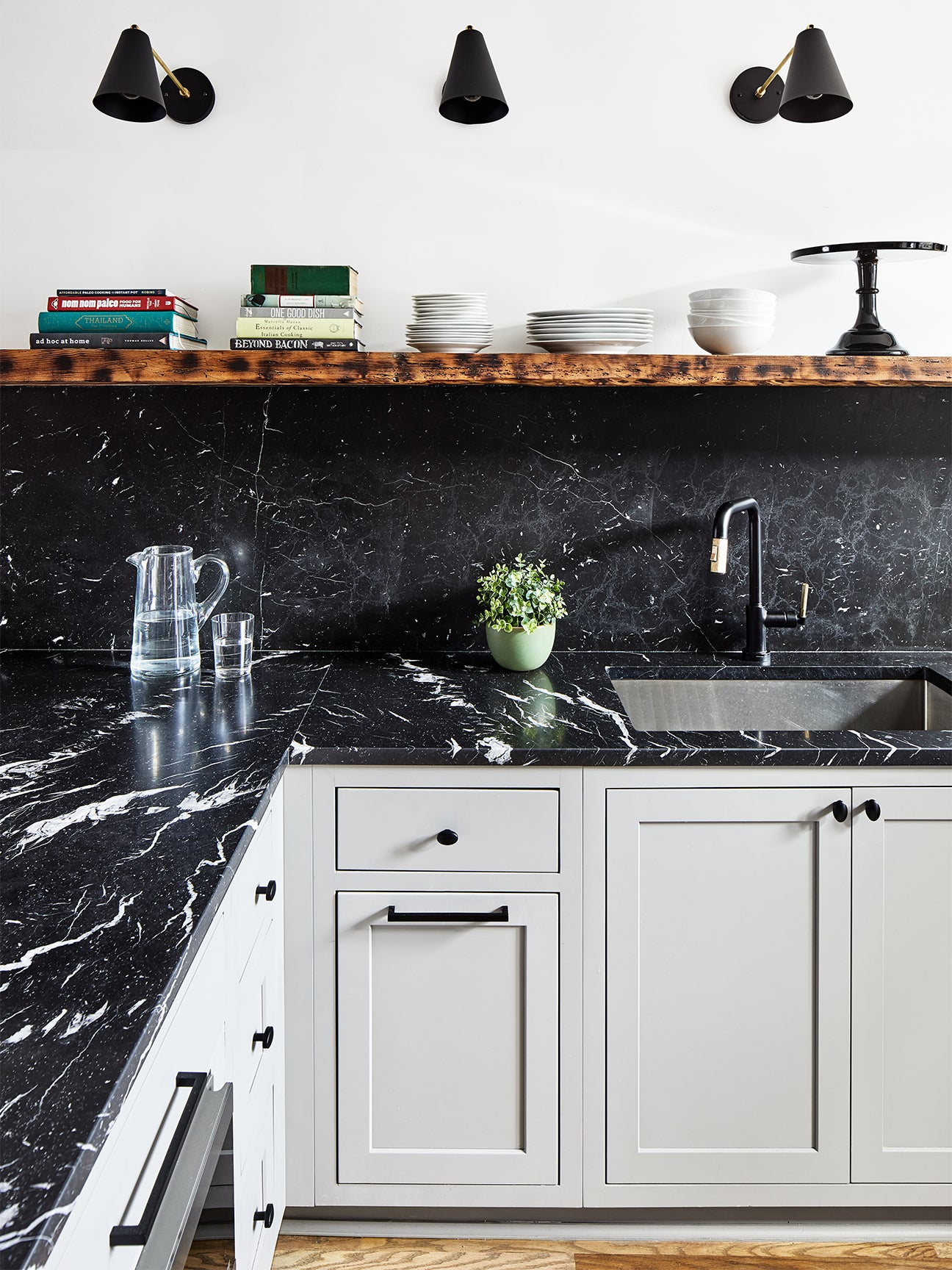 dark marble counters with cool gray cabinets and open wood shelving