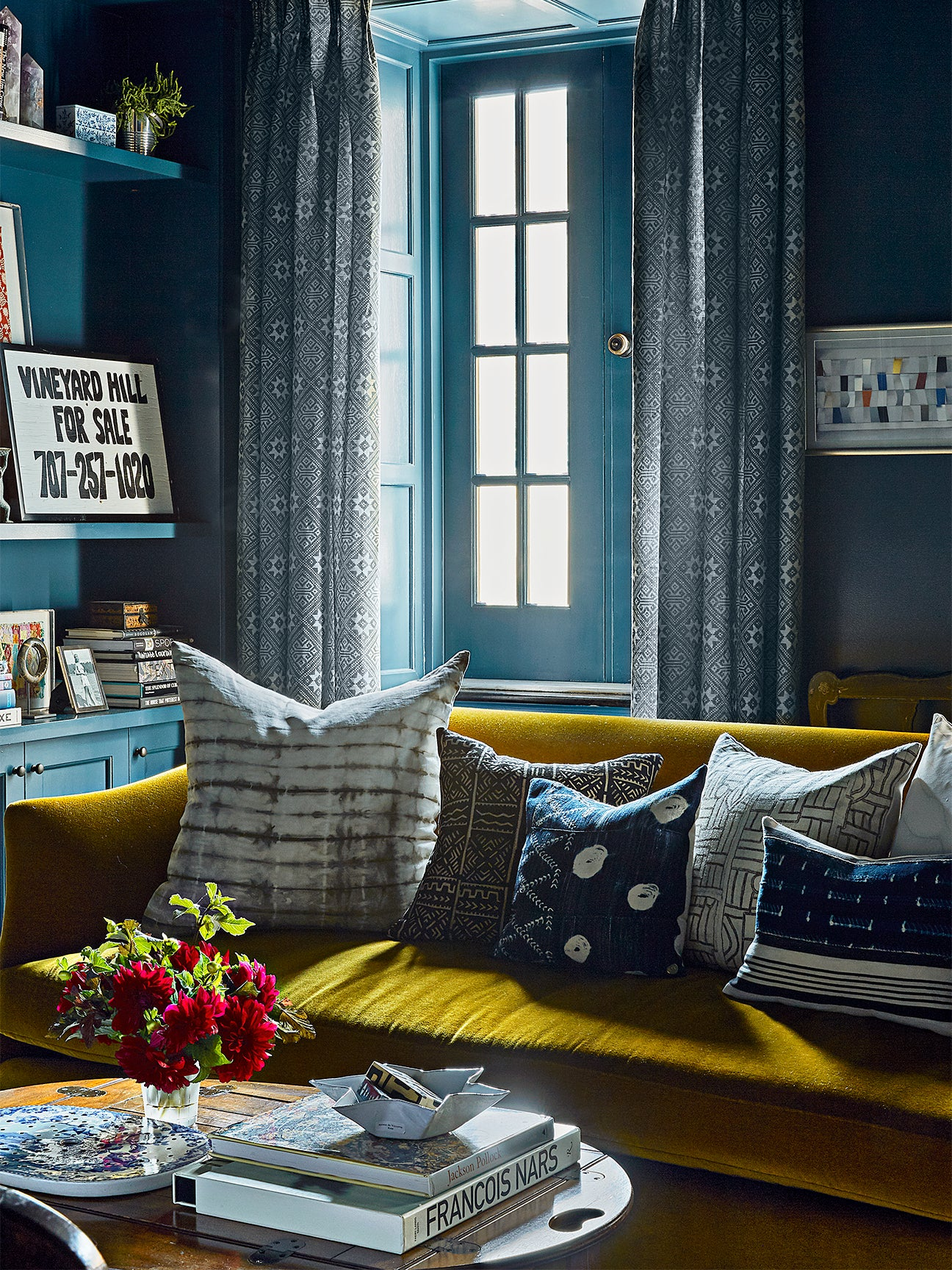 Small living room with navy walls and citrine sofa